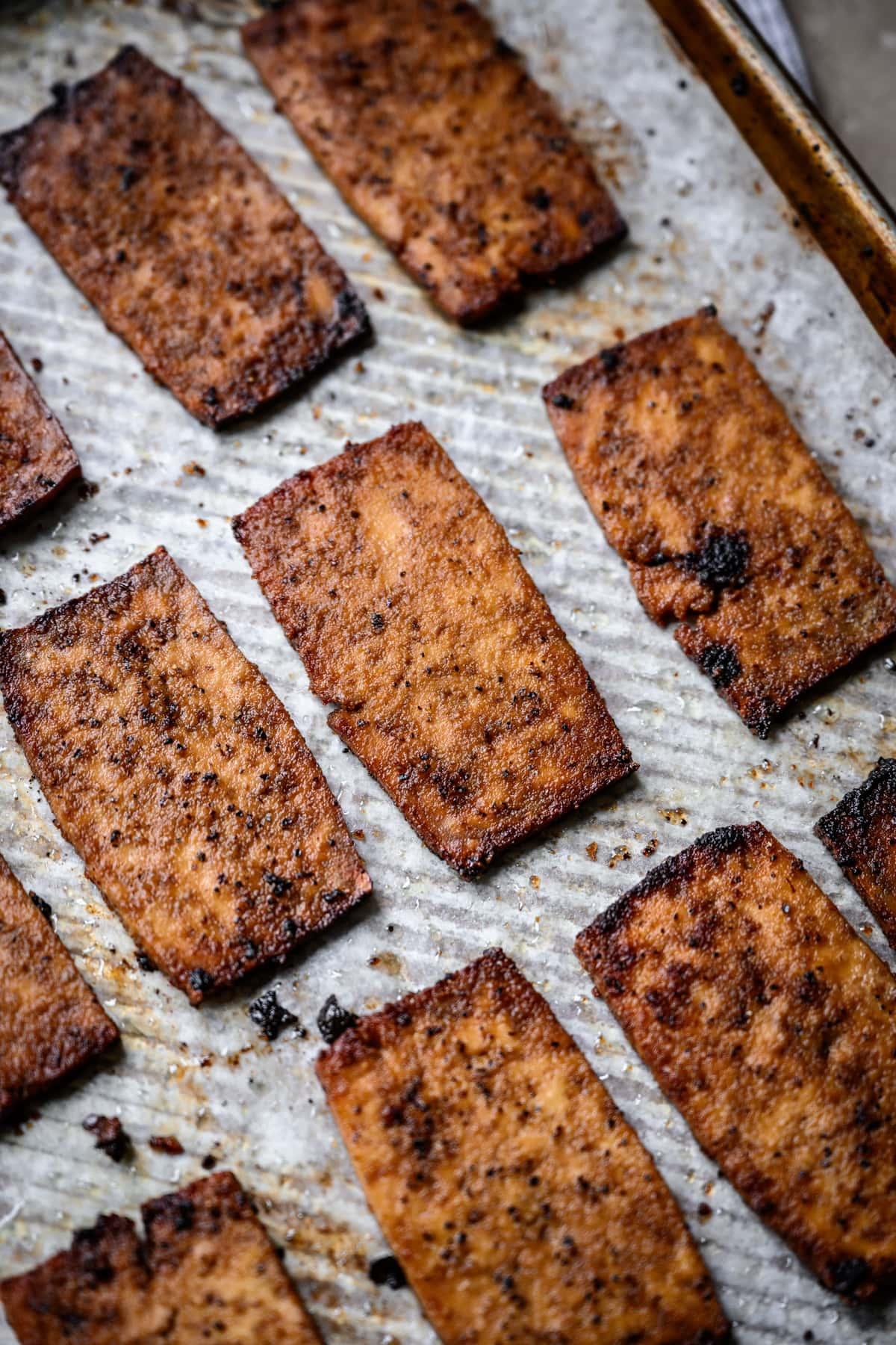 side view of vegan tofu bacon on sheet pan