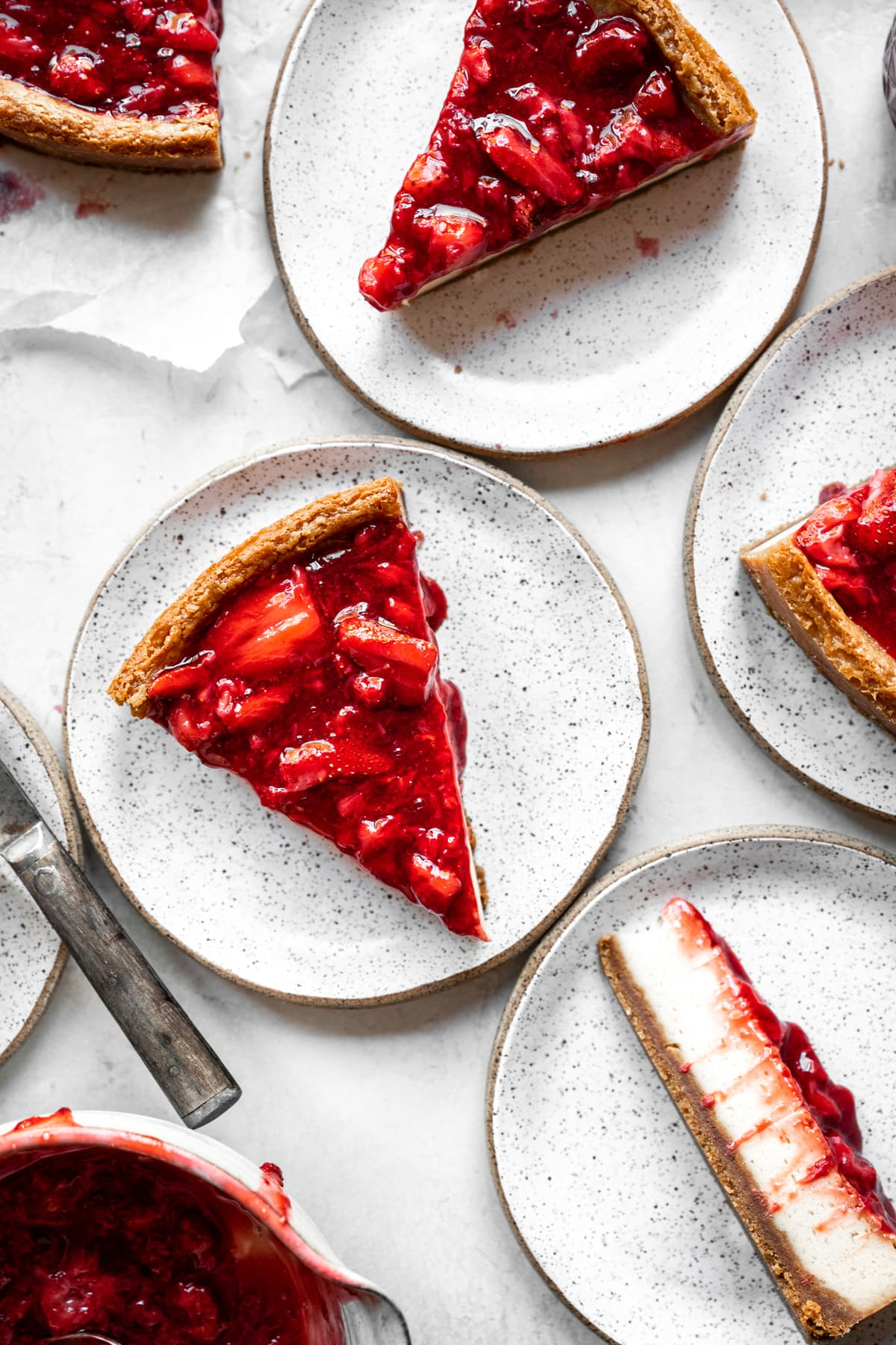 overhead view of slices of baked strawberry vegan cheesecake on small plates