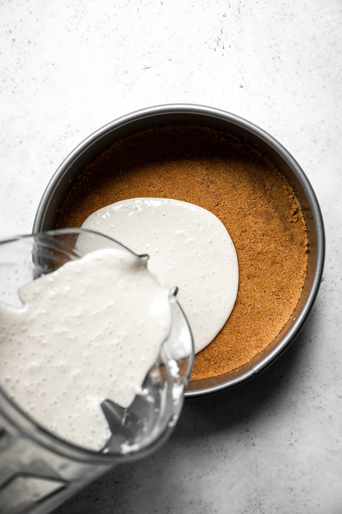 pouring vegan cheesecake filling into graham cracker crust