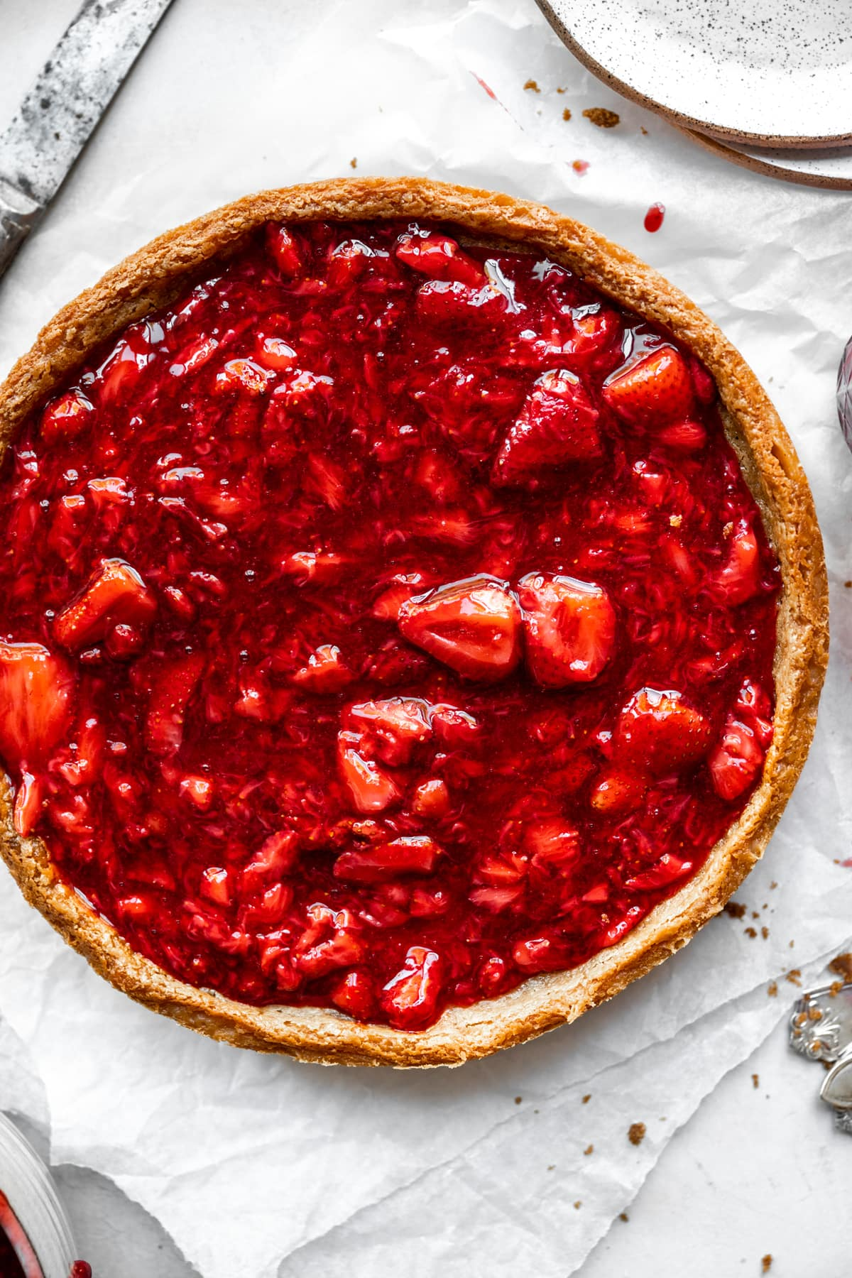 overhead view of classic vegan cheesecake with strawberry sauce
