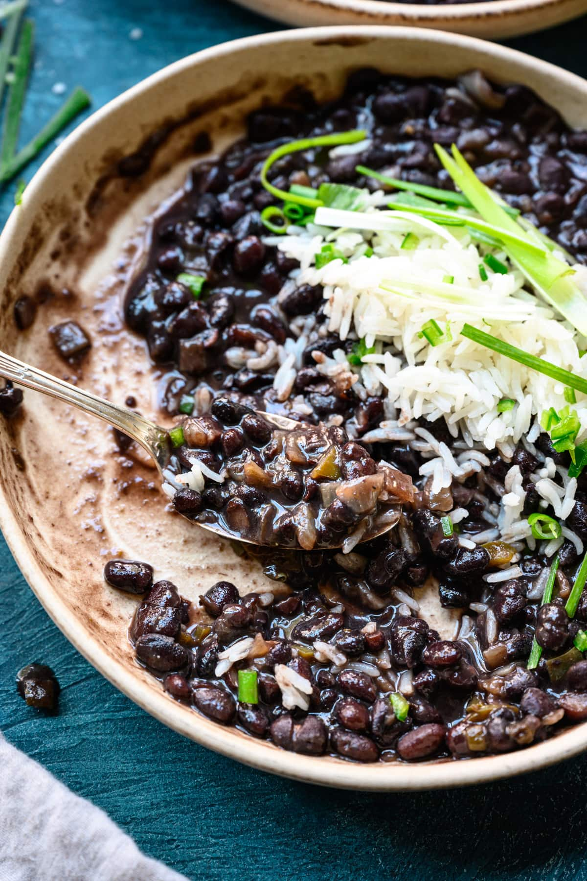 close up view of cuban-style black beans on spoon in bowl