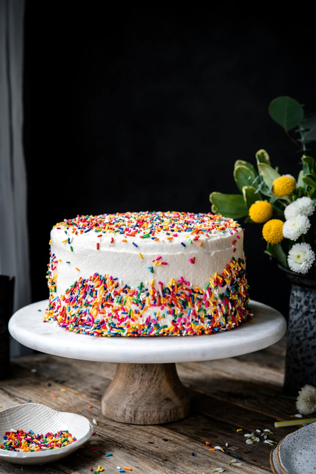 side view of vegan gluten free sprinkle cake on marble cake stand