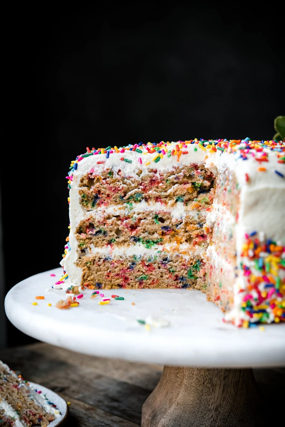 close up side view of slice of vegan gluten free funfetti cake with 3 layers