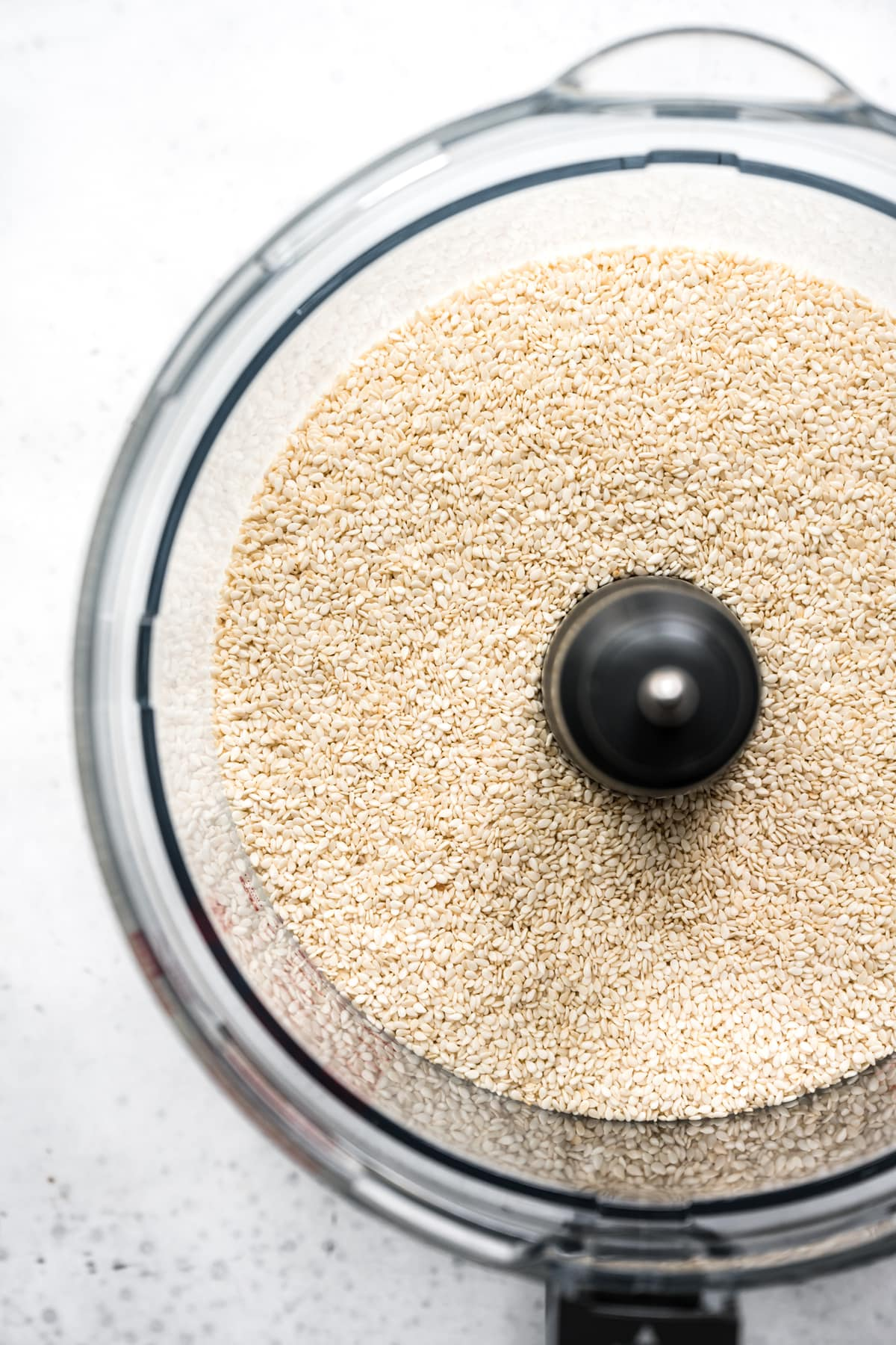 overhead view of hulled sesame seeds in food processor