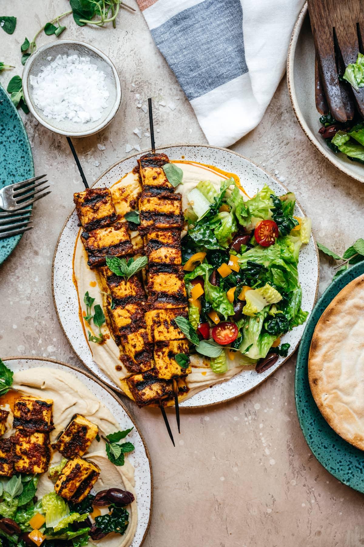 Mediterranean tofu kebabs over hummus with a salad