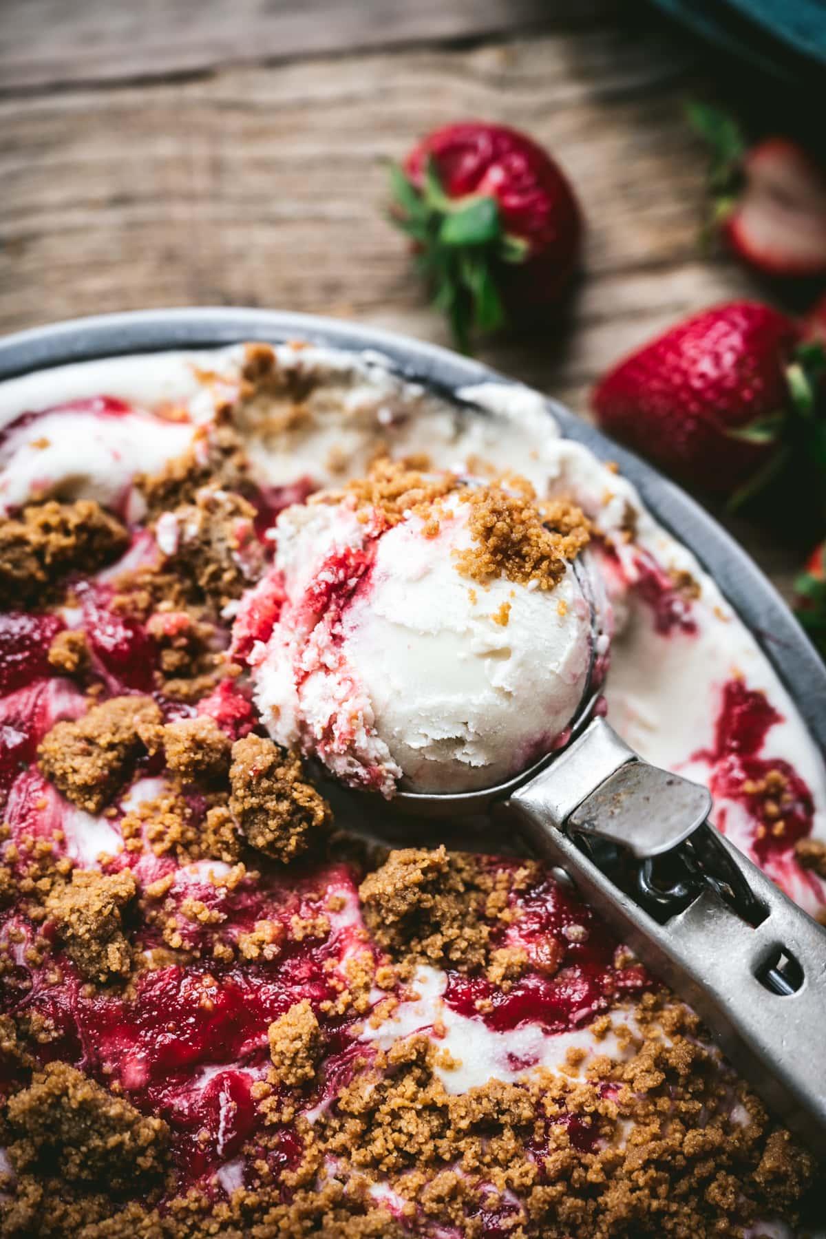 close up view of vegan strawberry cheesecake ice cream on ice cream scoop