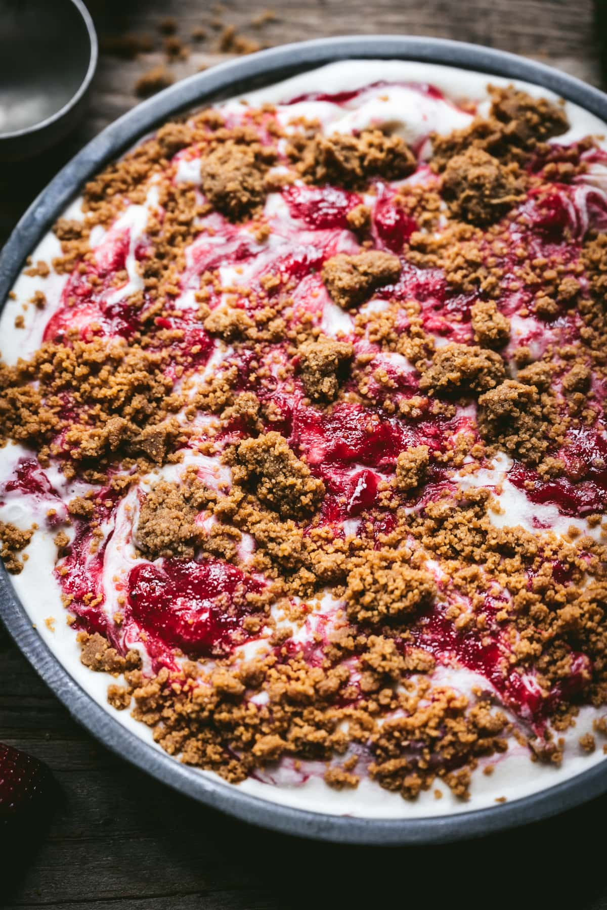 close up view of strawberry cheesecake ice cream with graham cracker streusel