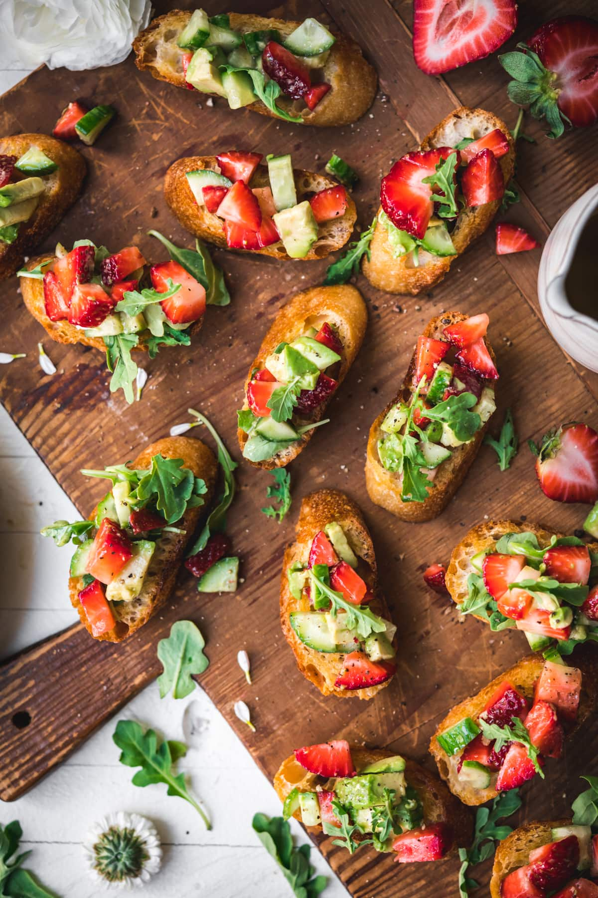 overhead view of summer crostini with strawberries avocado and cucumber