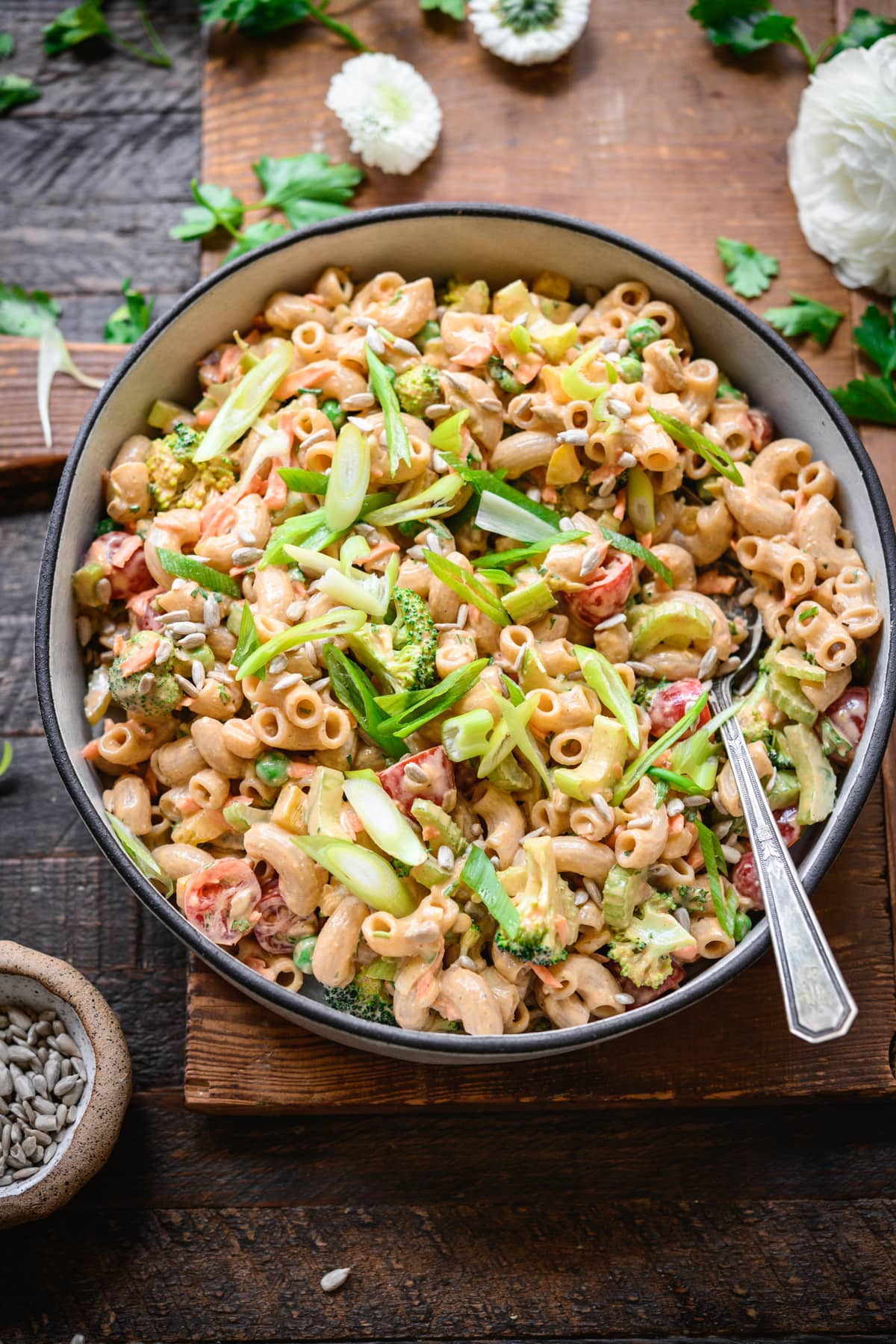 overhead view of vegan macaroni salad in a bowl with fresh vegetables