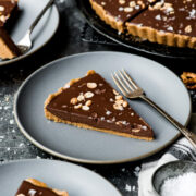 side view of slice of vegan chocolate tart on plate