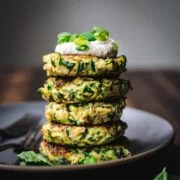 side view of stack of vegan zucchini fritters on a plate