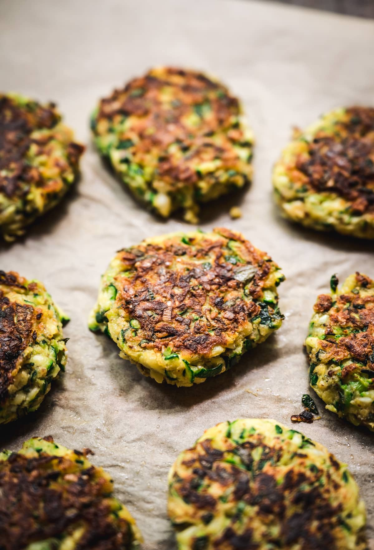 side view of vegan zucchini fritters on parchment paper