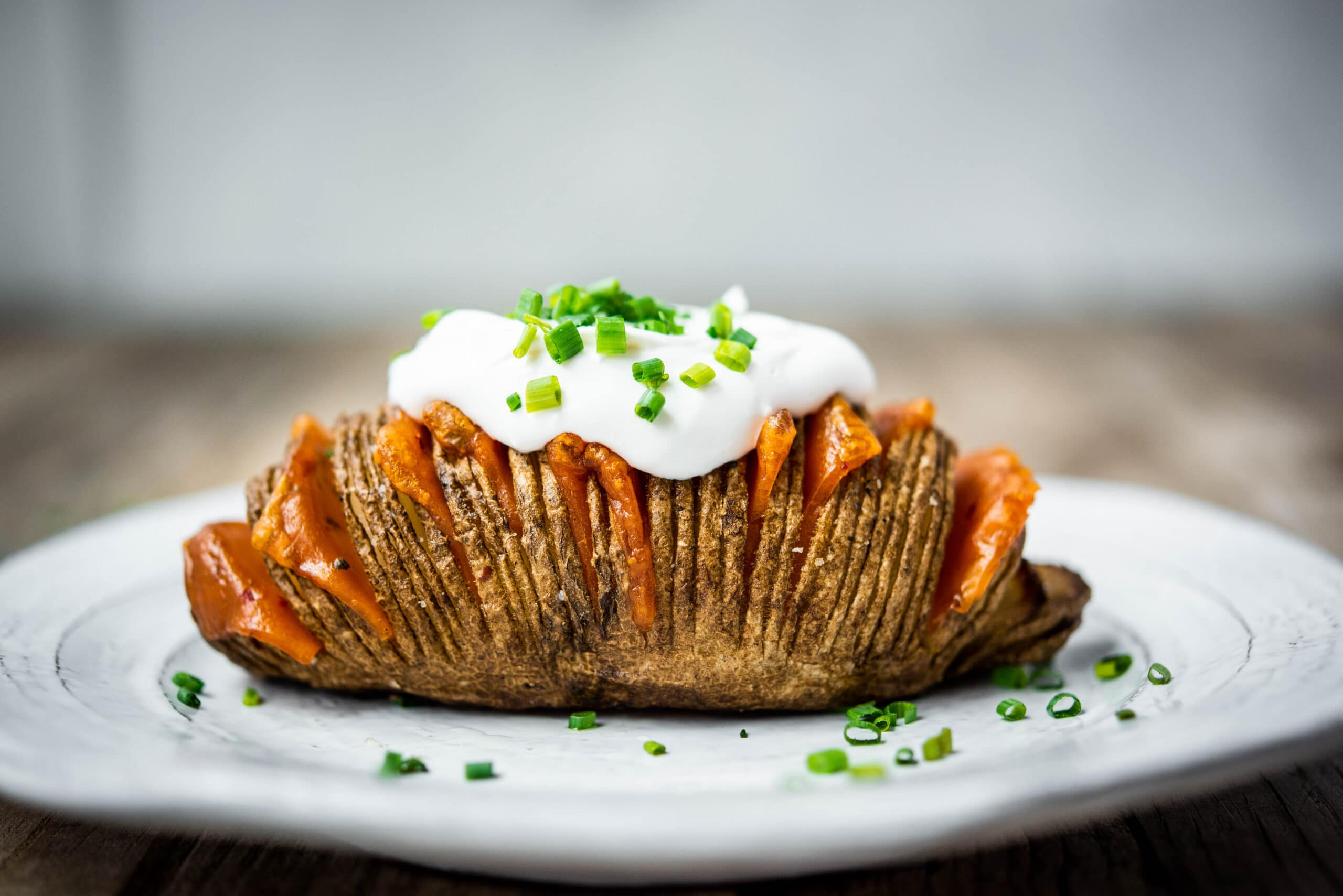 side view of cheesy hasselback potato on plate