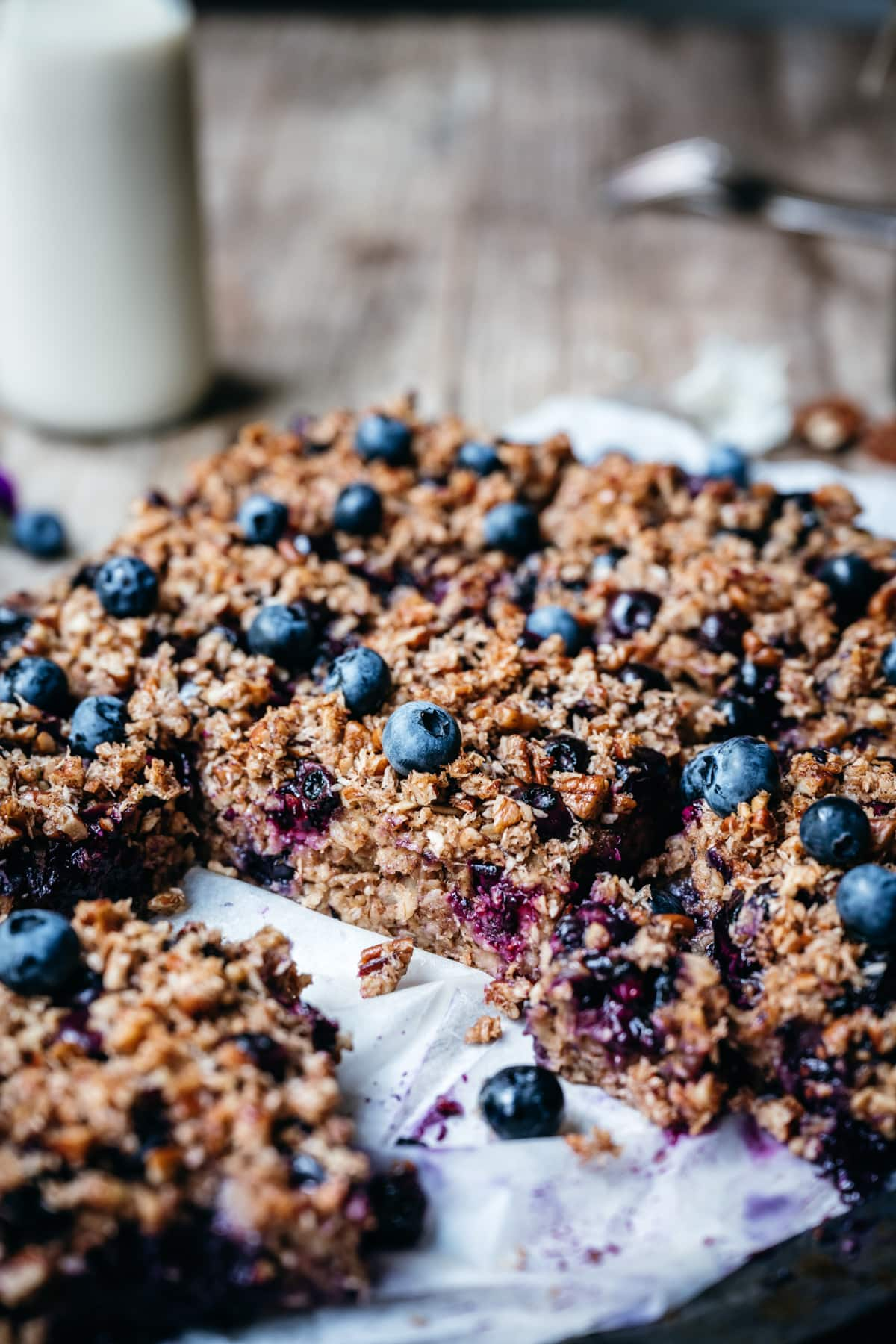 side view of blueberry oatmeal bake on parchment paper
