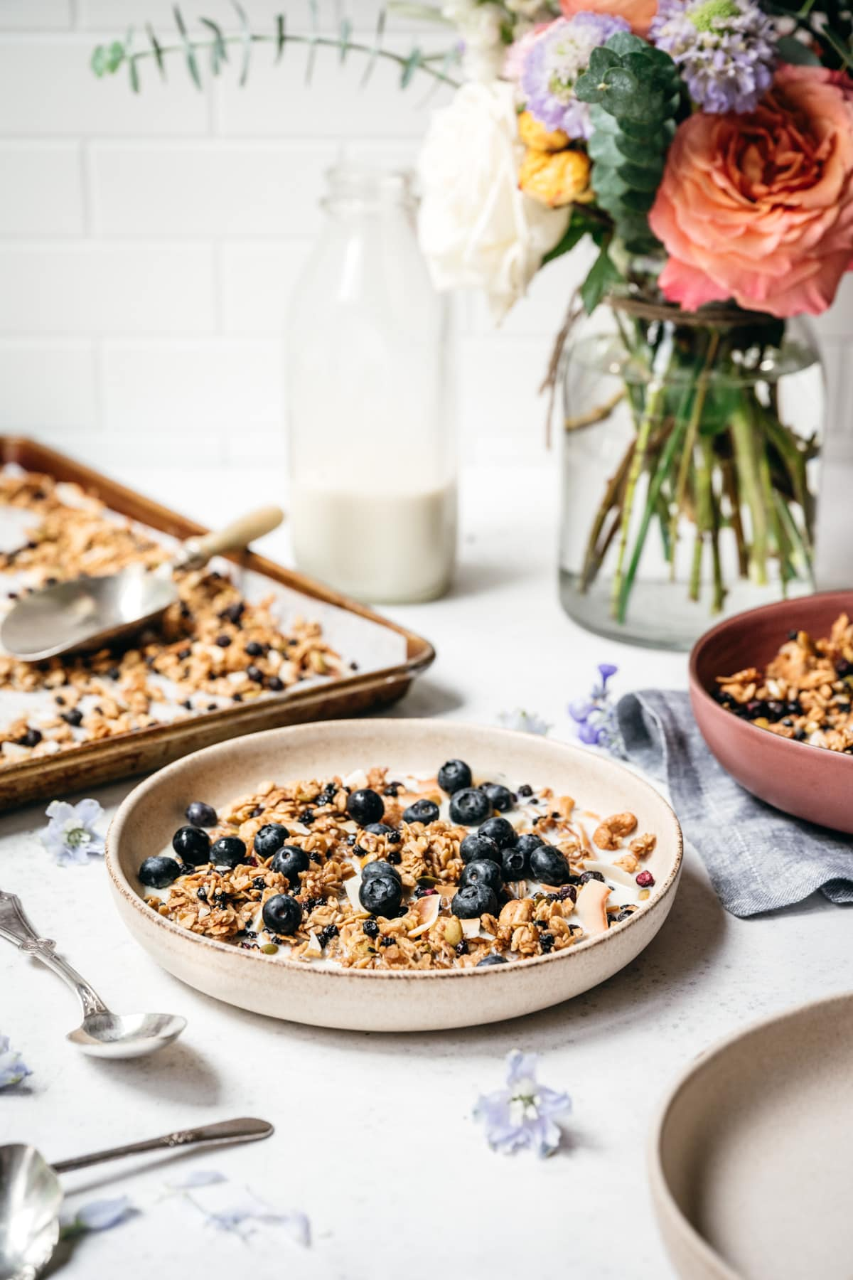 side view of blueberry lemon granola in a bowl with milk and blueberries