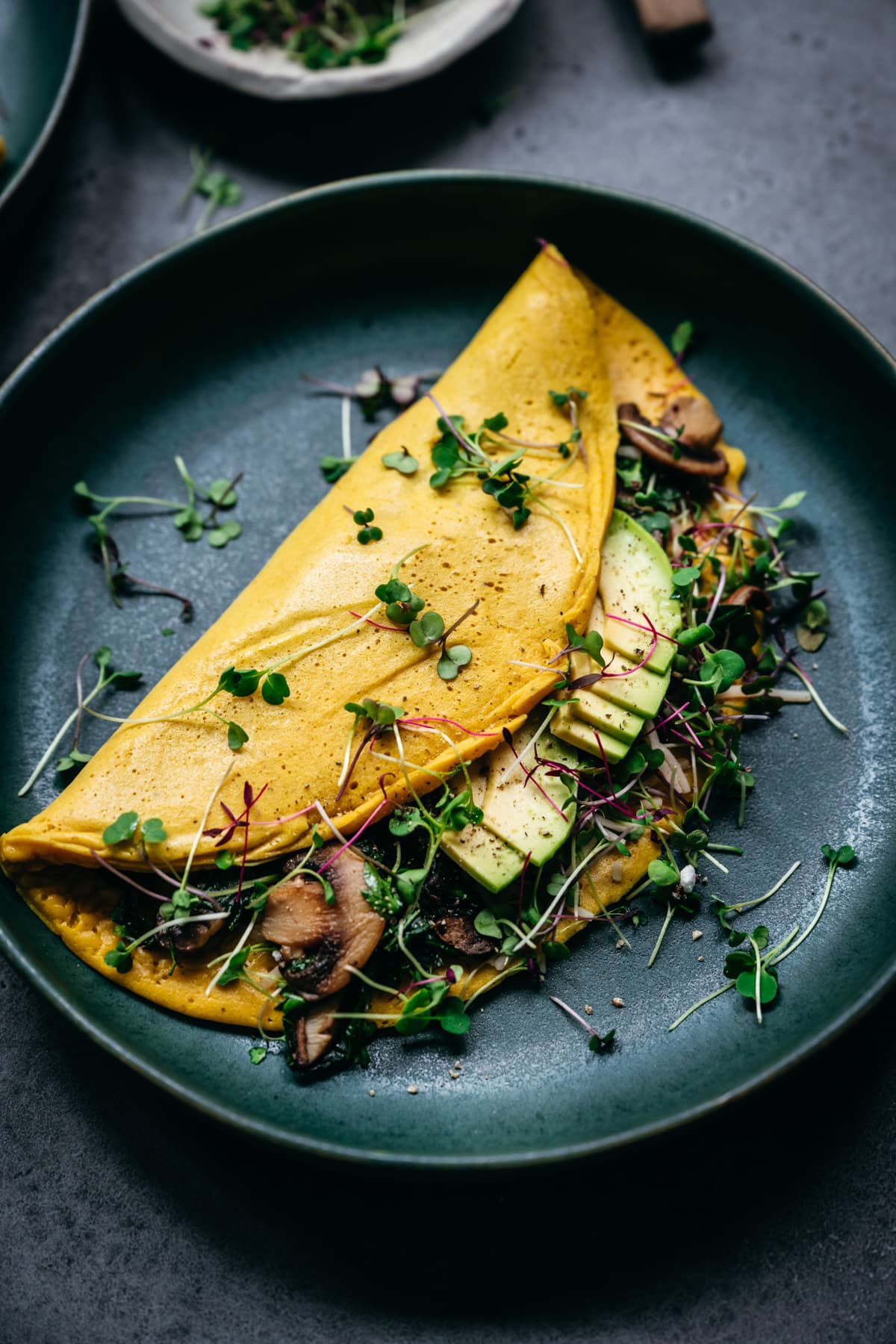close up view of vegan omelette with mushrooms and avocado.