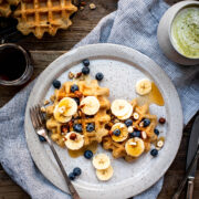 Waffles on a plate from above with bananas and blueberries.