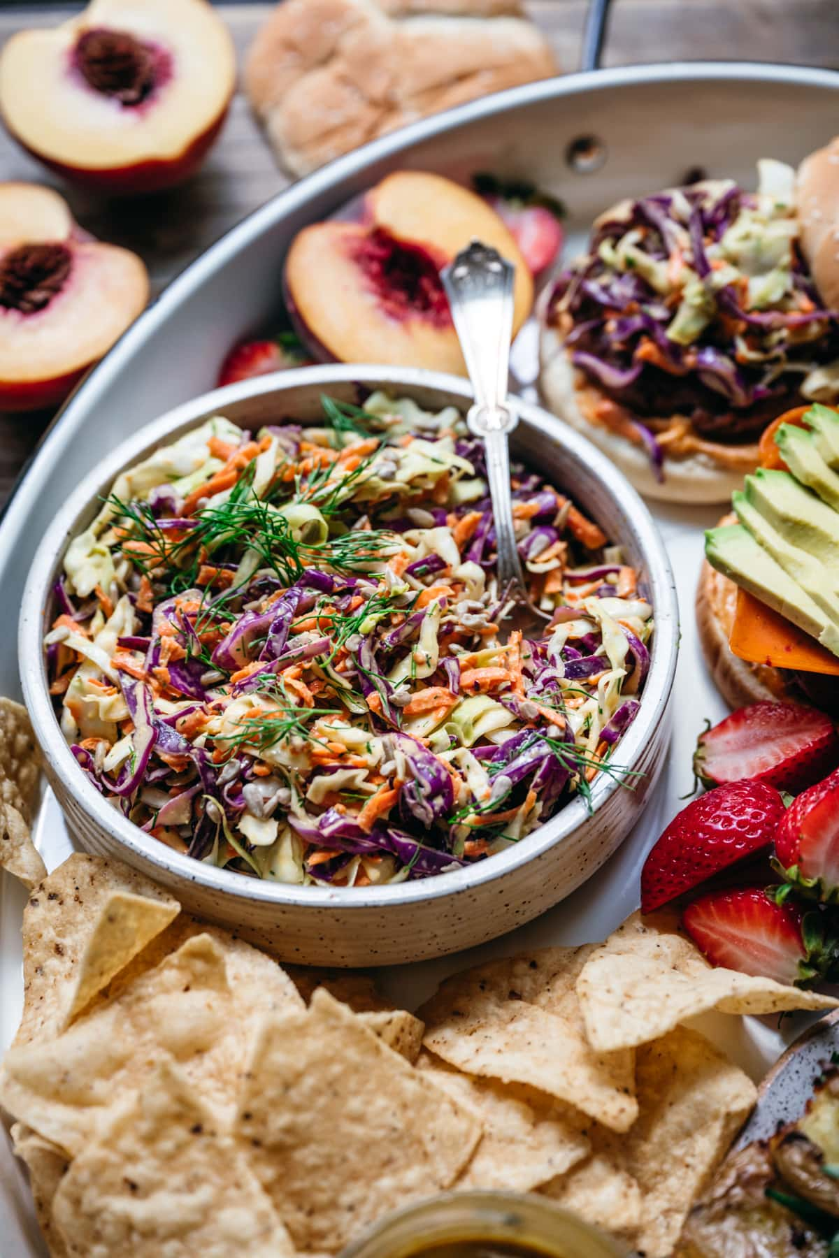 side view of classic vegan coleslaw in white bowl surrounded by tortilla chips and veggie burgers.
