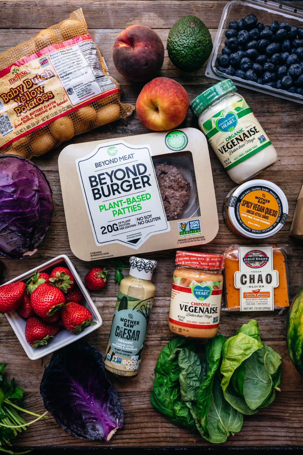 overhead view of vegan summer bbq ingredients and products on wood table.