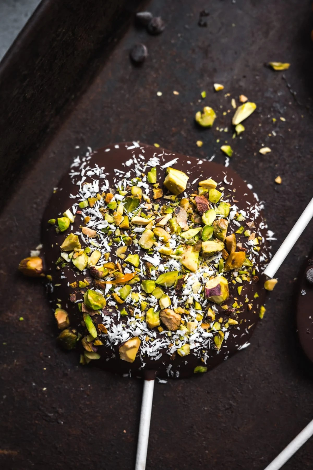 overhead view of chocolate covered apple slice with coconut and pistachios.