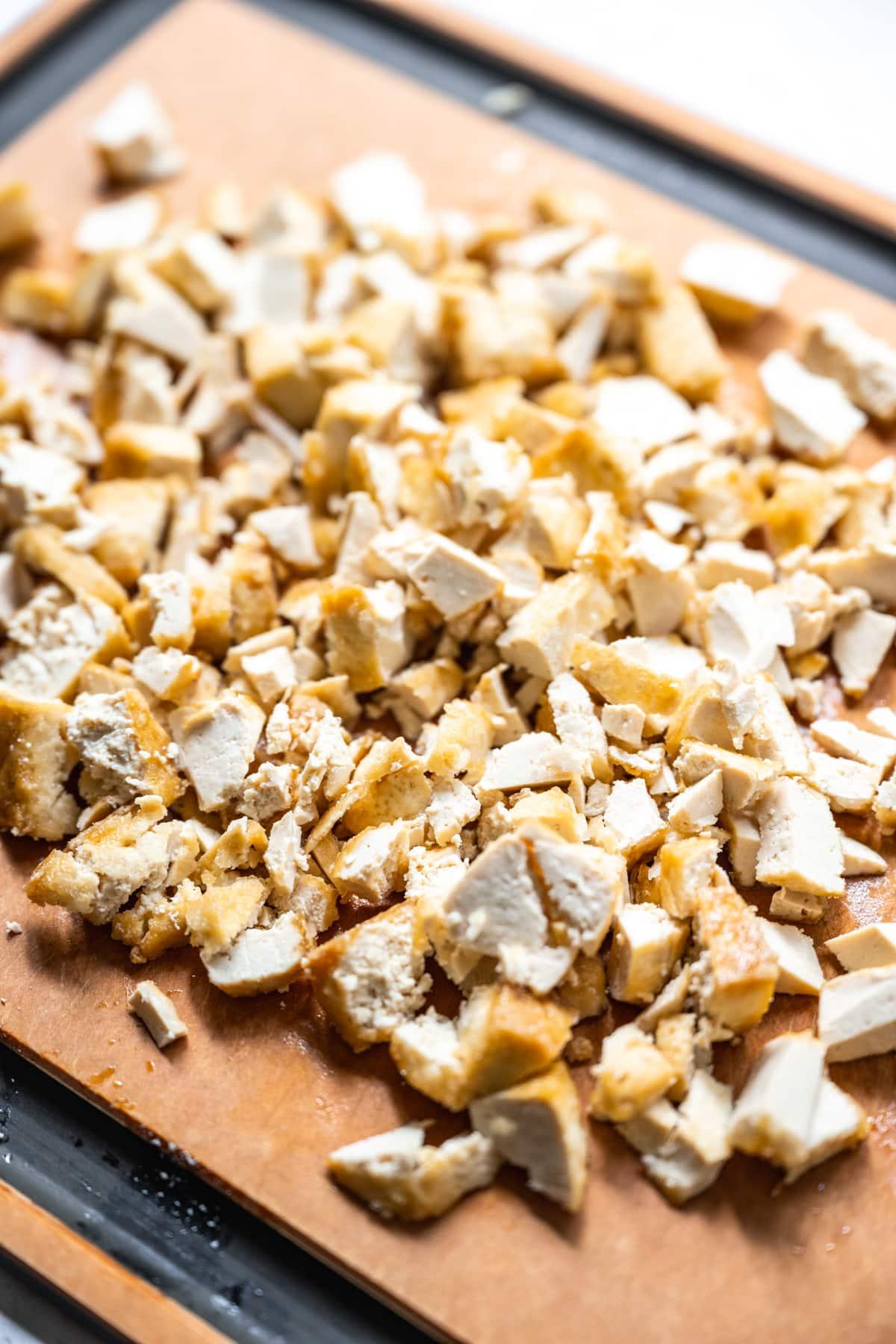 close up view of chopped, crispy tofu on a cutting board.