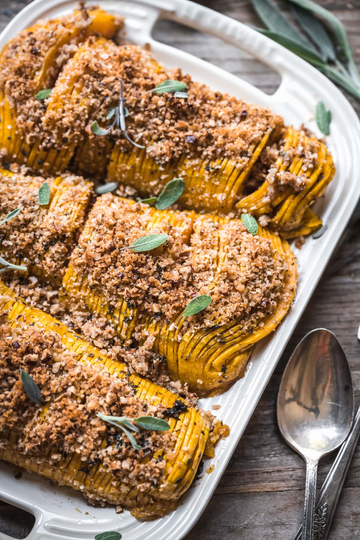 close up view of hasselback butternut squash topped with breadcrumbs.