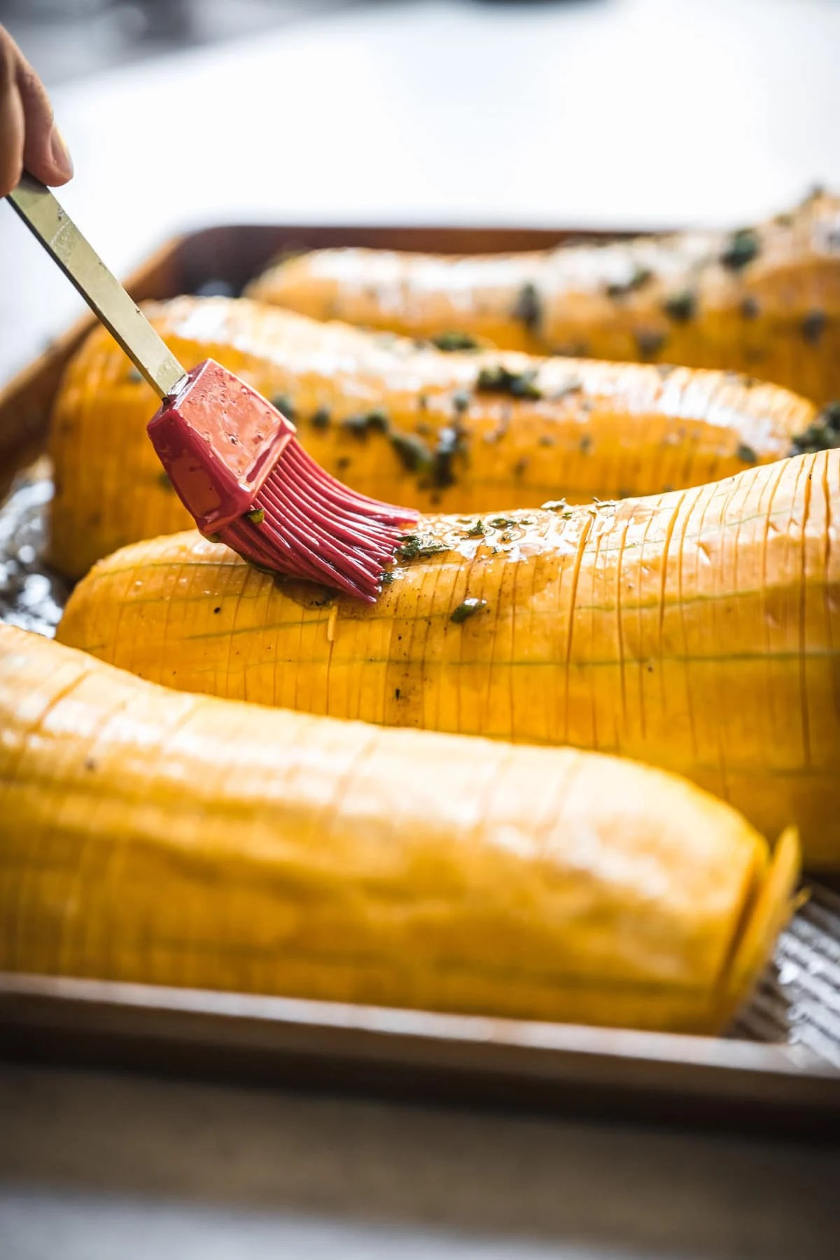 person brushing maple herb butter on hasselback butternut squash.