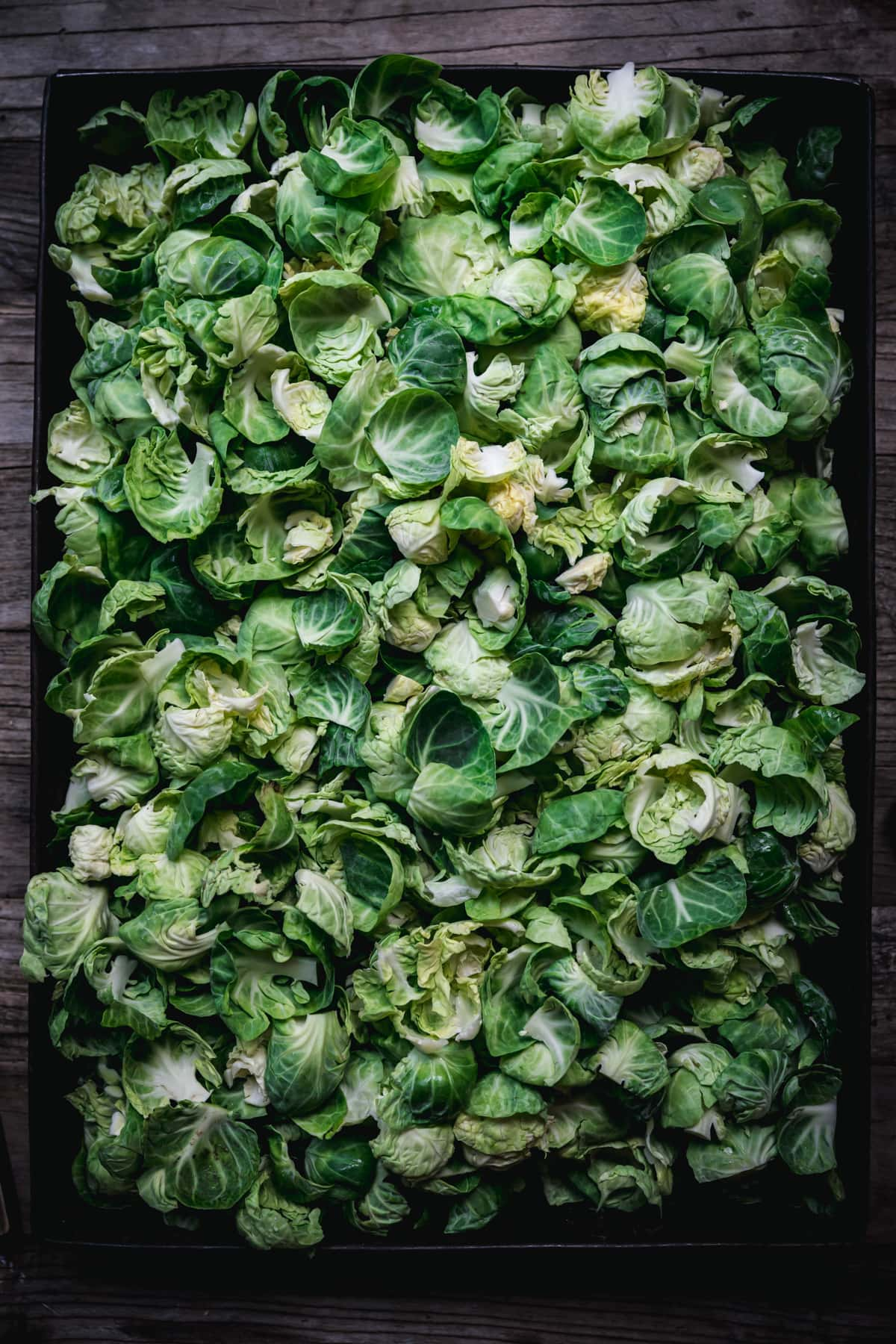 overhead view of raw brussels sprout leaves in a large pan.