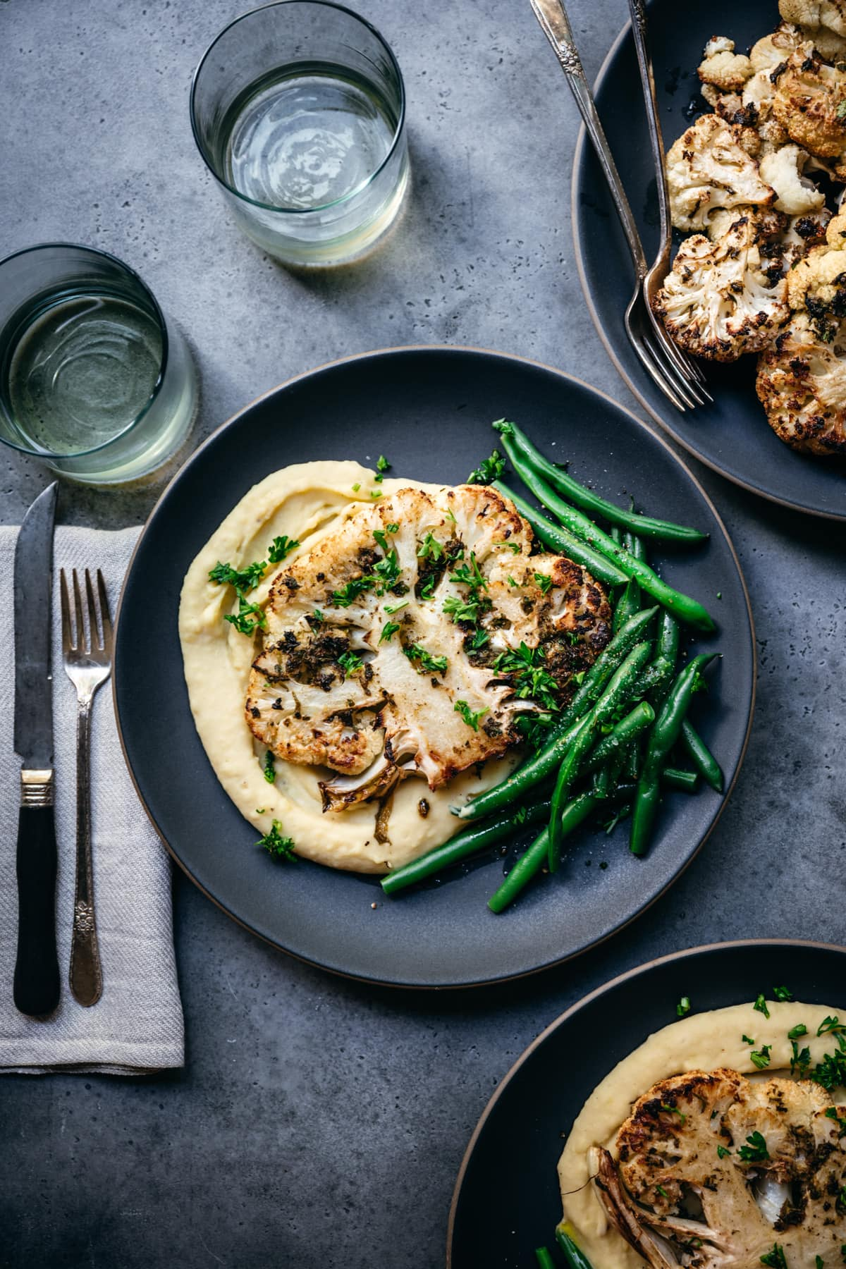 overhead view of roasted cauliflower steak on a plate with mashed potatoes and green beans.