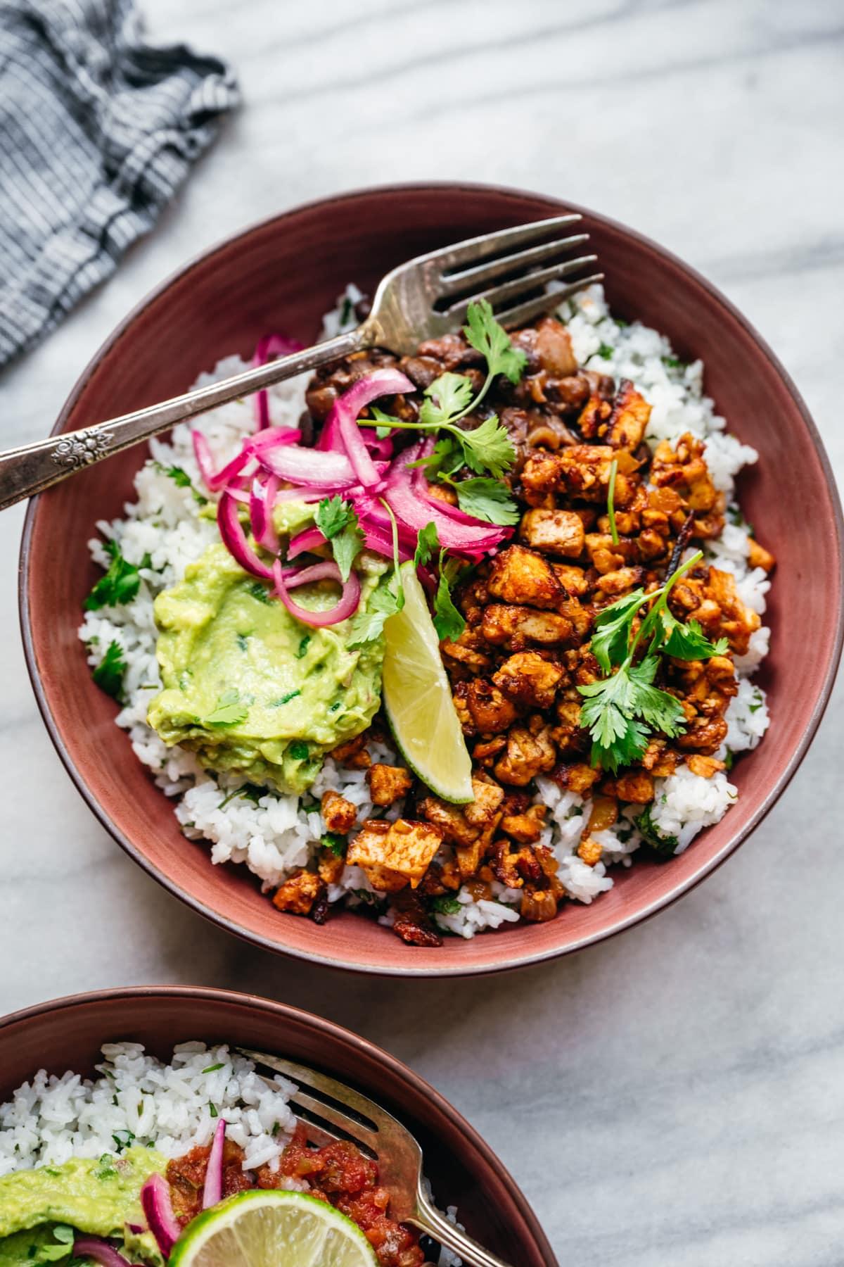 overhead view of vegan burrito bowl with sofritas tofu, guacamole and rice.