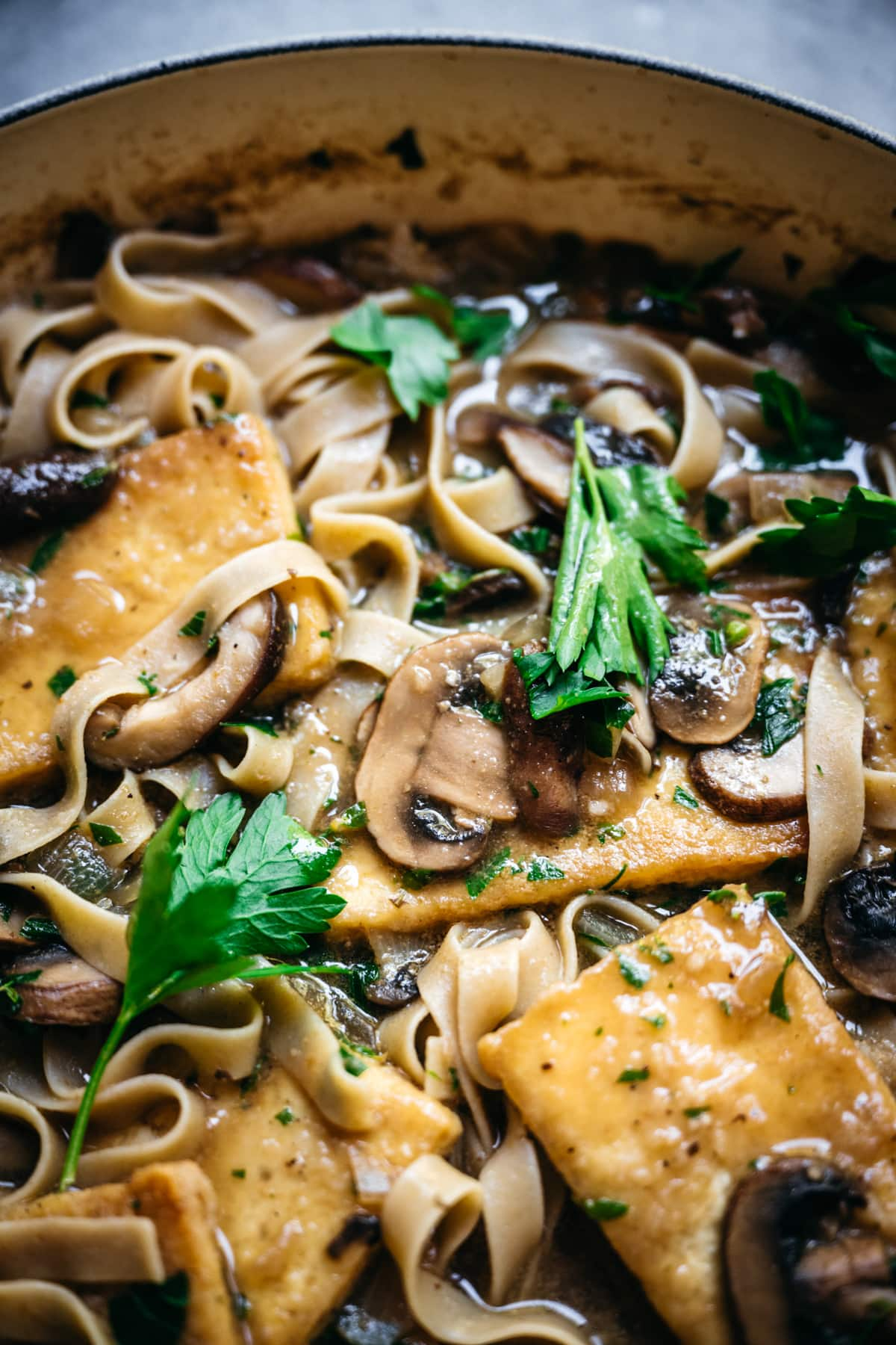 close up view of a mushroom in a pan of tofu marsala.