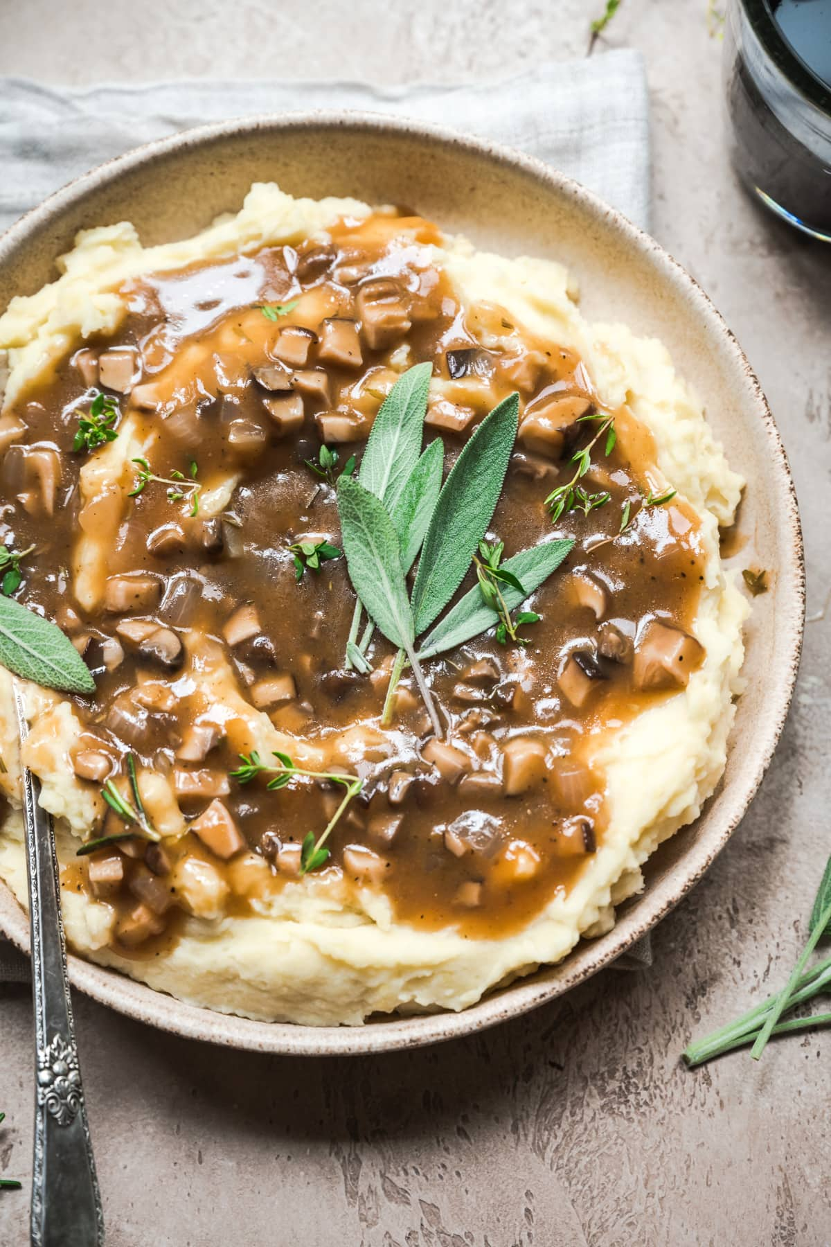 close up view of bowl of mashed potatoes topped with vegan mushroom gravy and fresh sage.