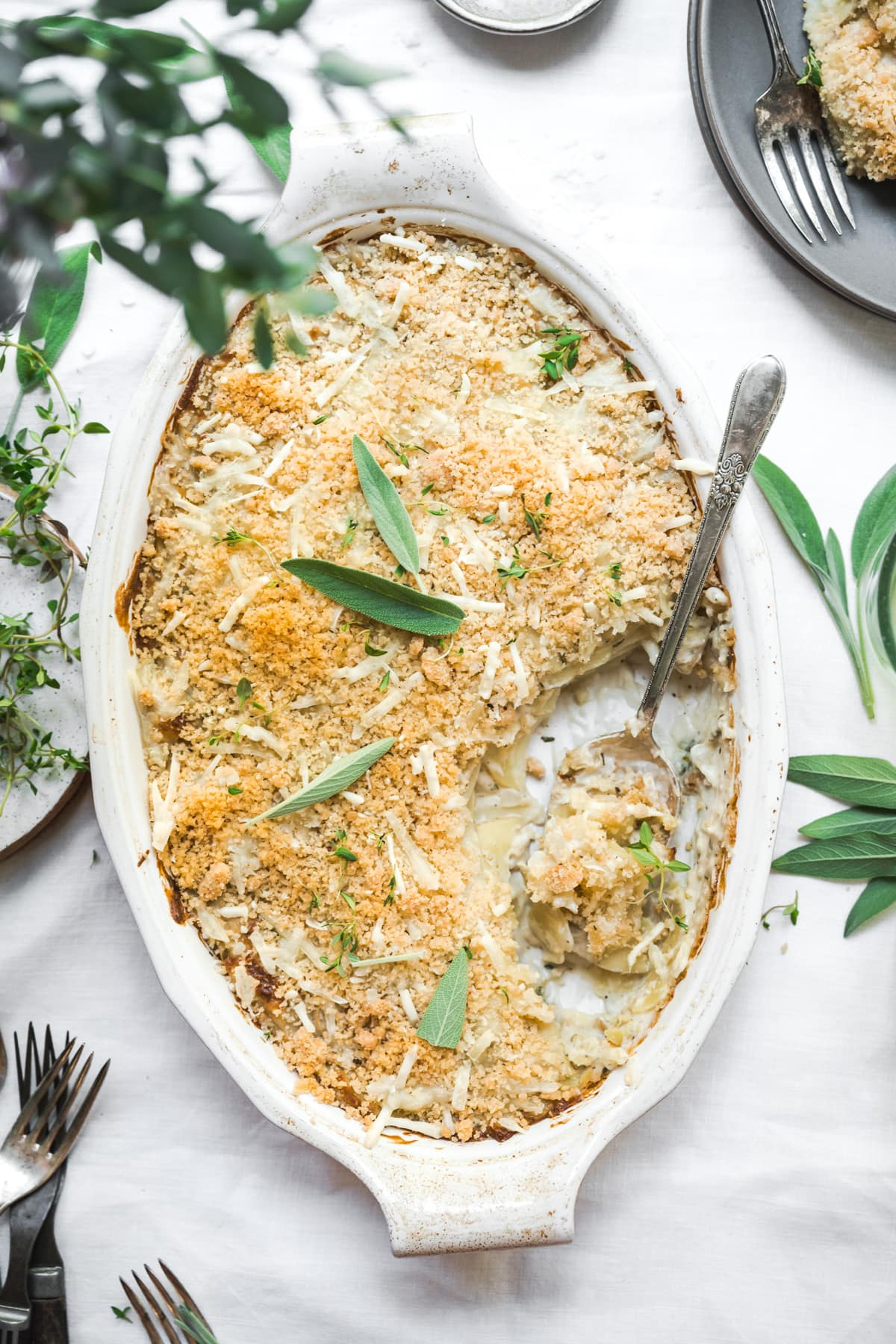 overhead view of vegan scalloped potatoes with breadcrumb topping in a casserole dish on white linen tablecloth.