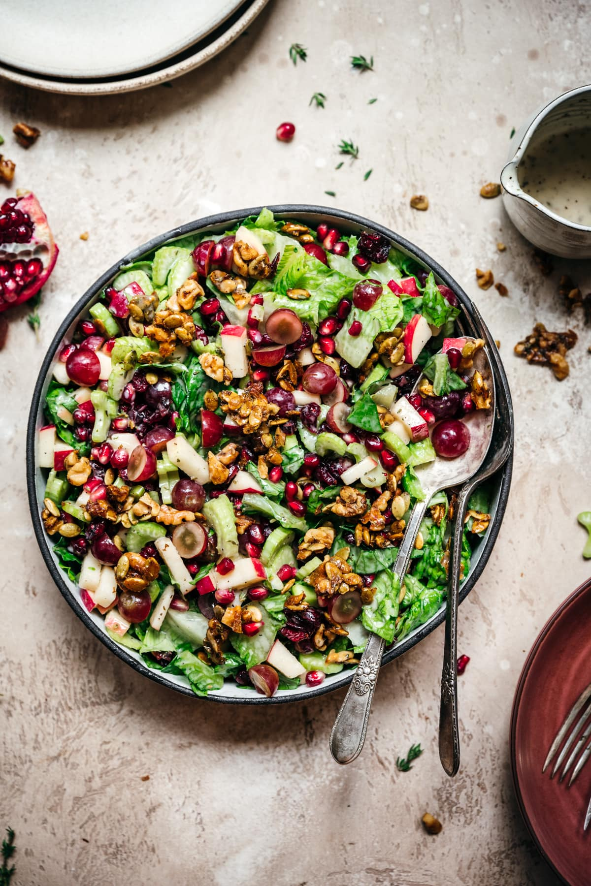 overhead view of vegan waldorf salad with walnut brittle and pomegranate in a bowl with serving utensils.