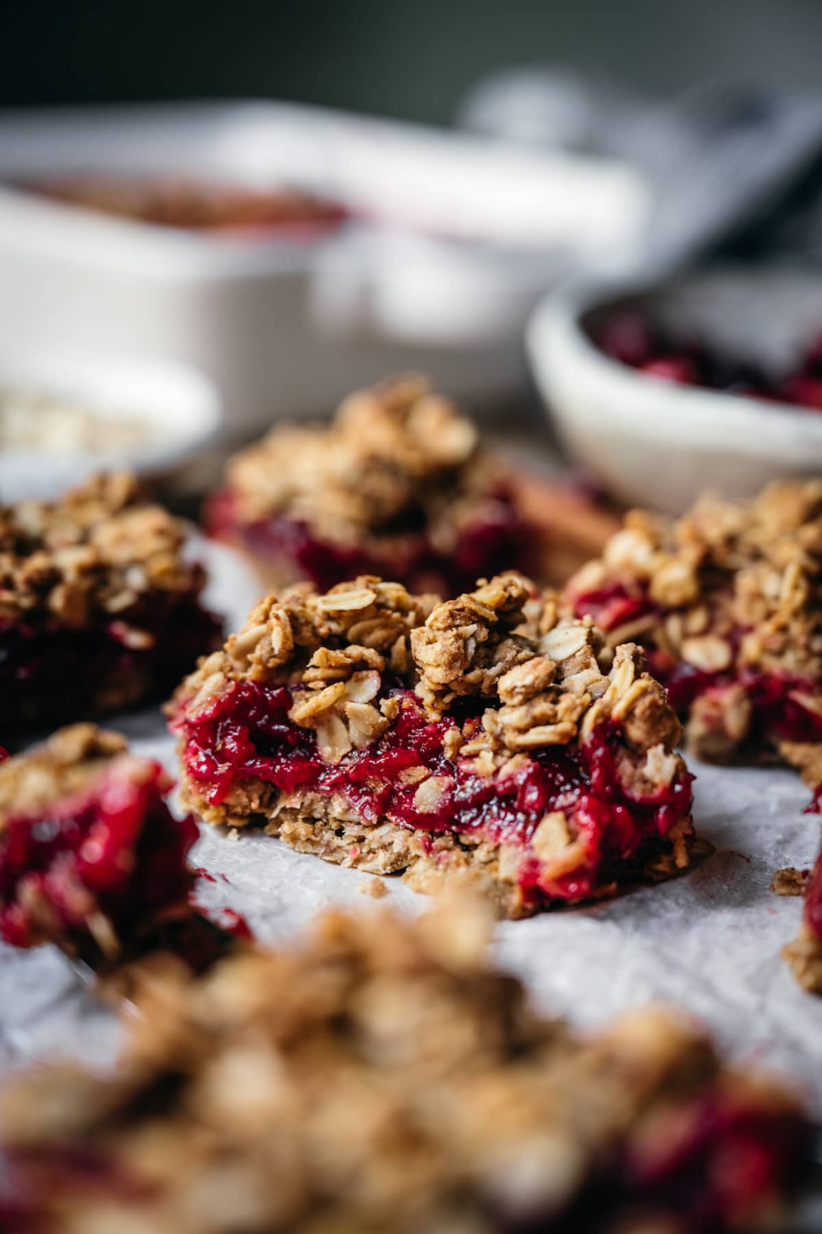 side view of vegan cranberry crumb bar cut in half with oat streusel topping.