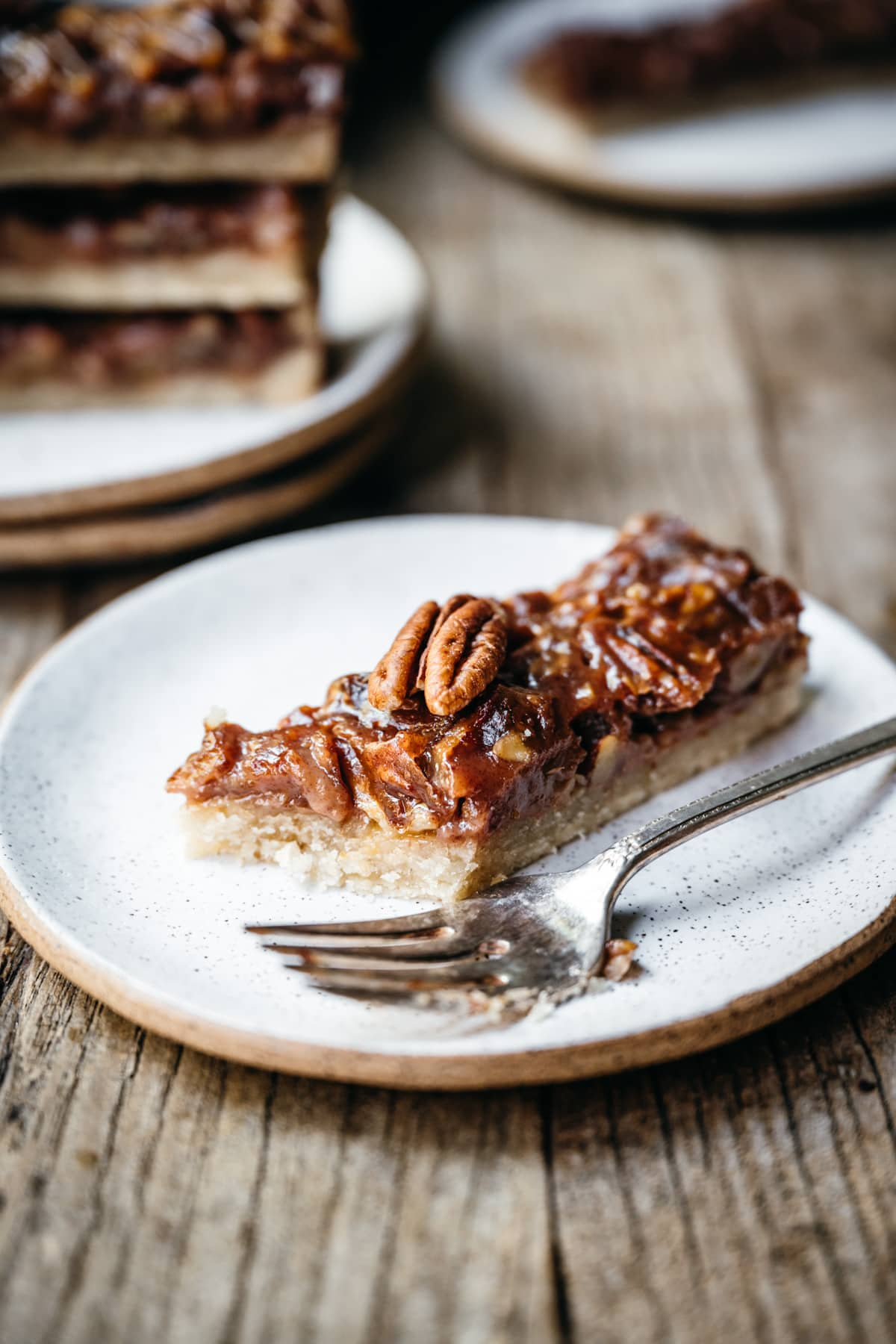 side view of vegan pecan pie caramel bar on a small plate.