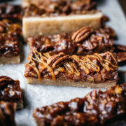 side view of vegan pecan pie bars with caramel topping.