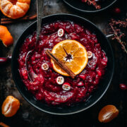 overhead view of cranberry sauce in a black bowl garnished with orange slice and cinnamon stick.