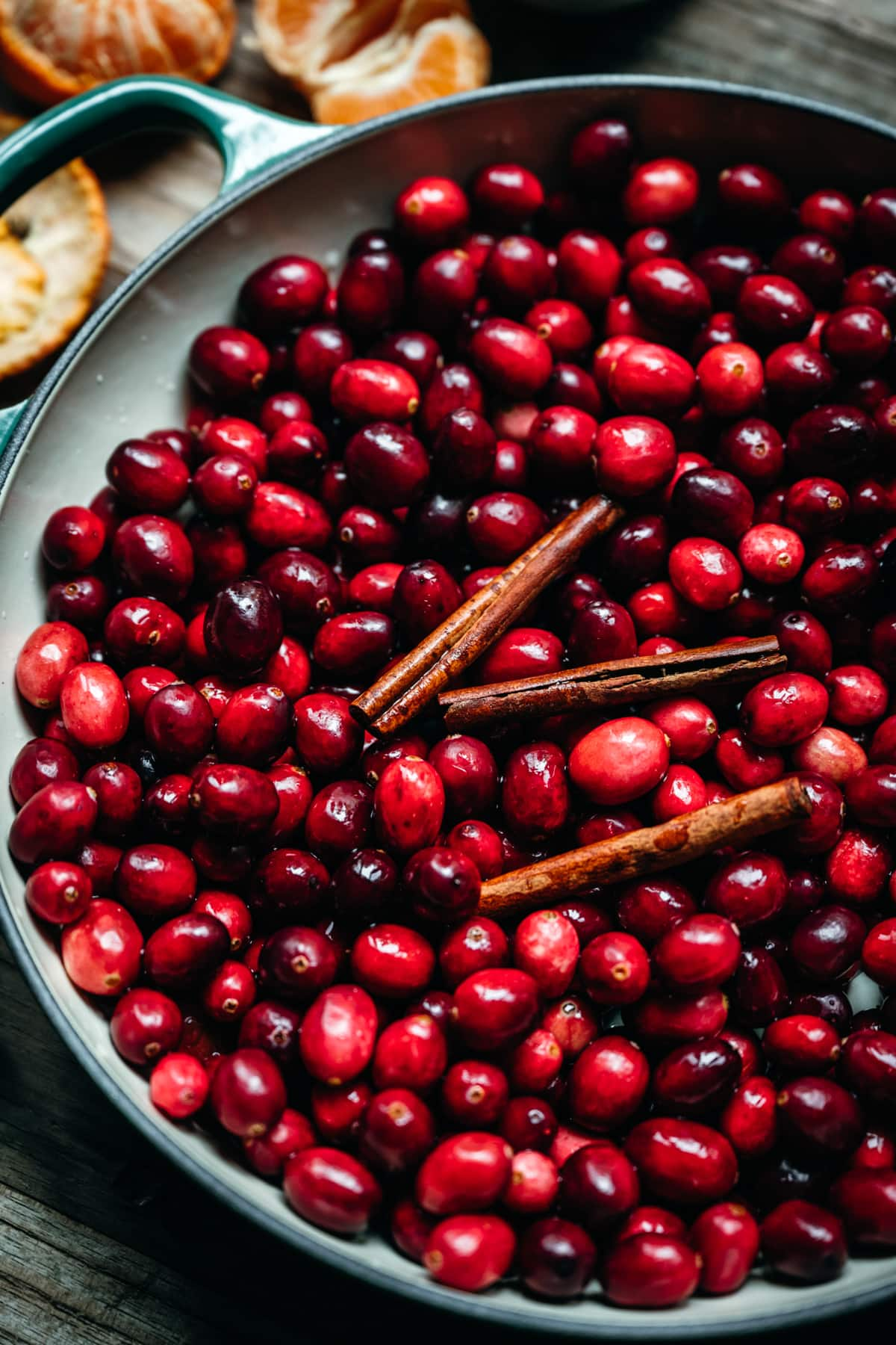 close up view of fresh cranberries in a pot with cinnamon sticks