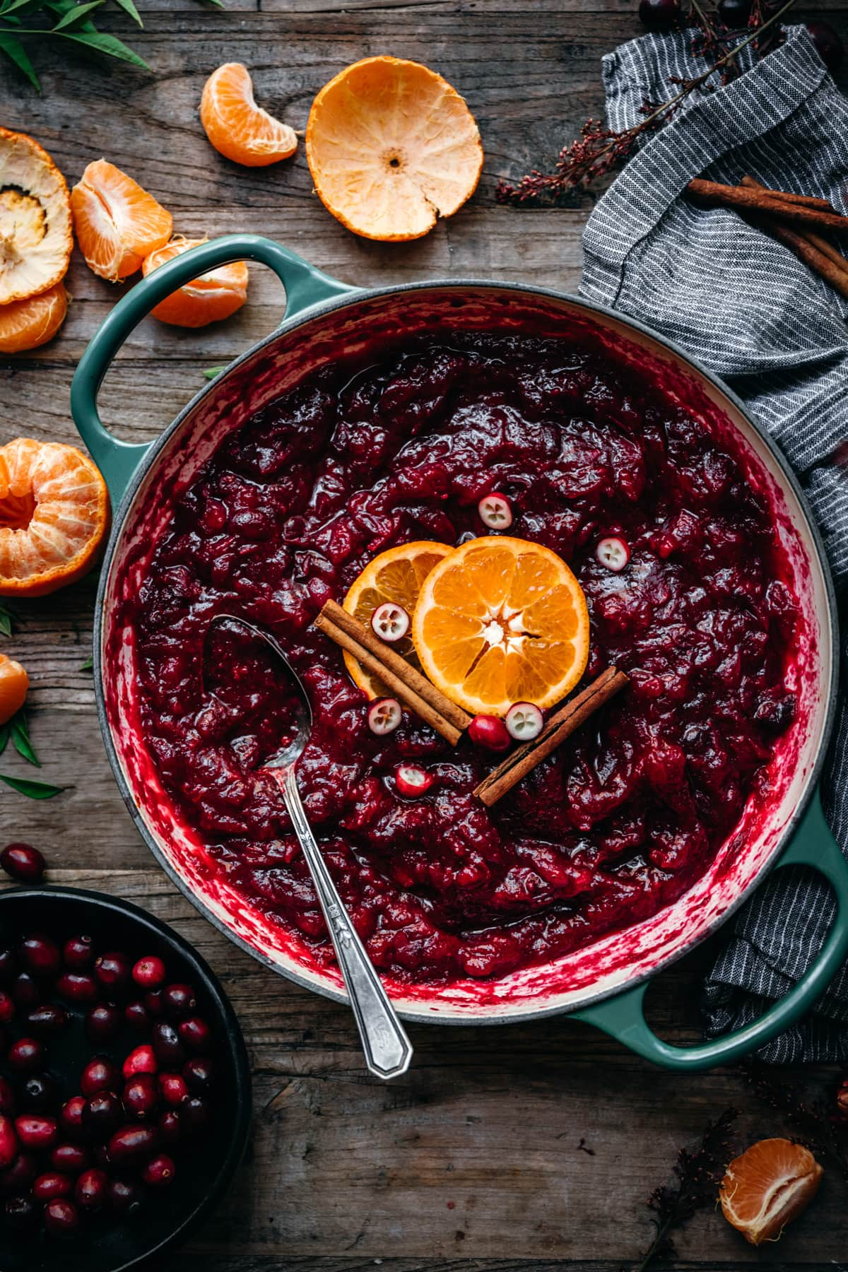 overhead view of cranberry sauce in a large pot garnished with orange slice and cinnamon stick.