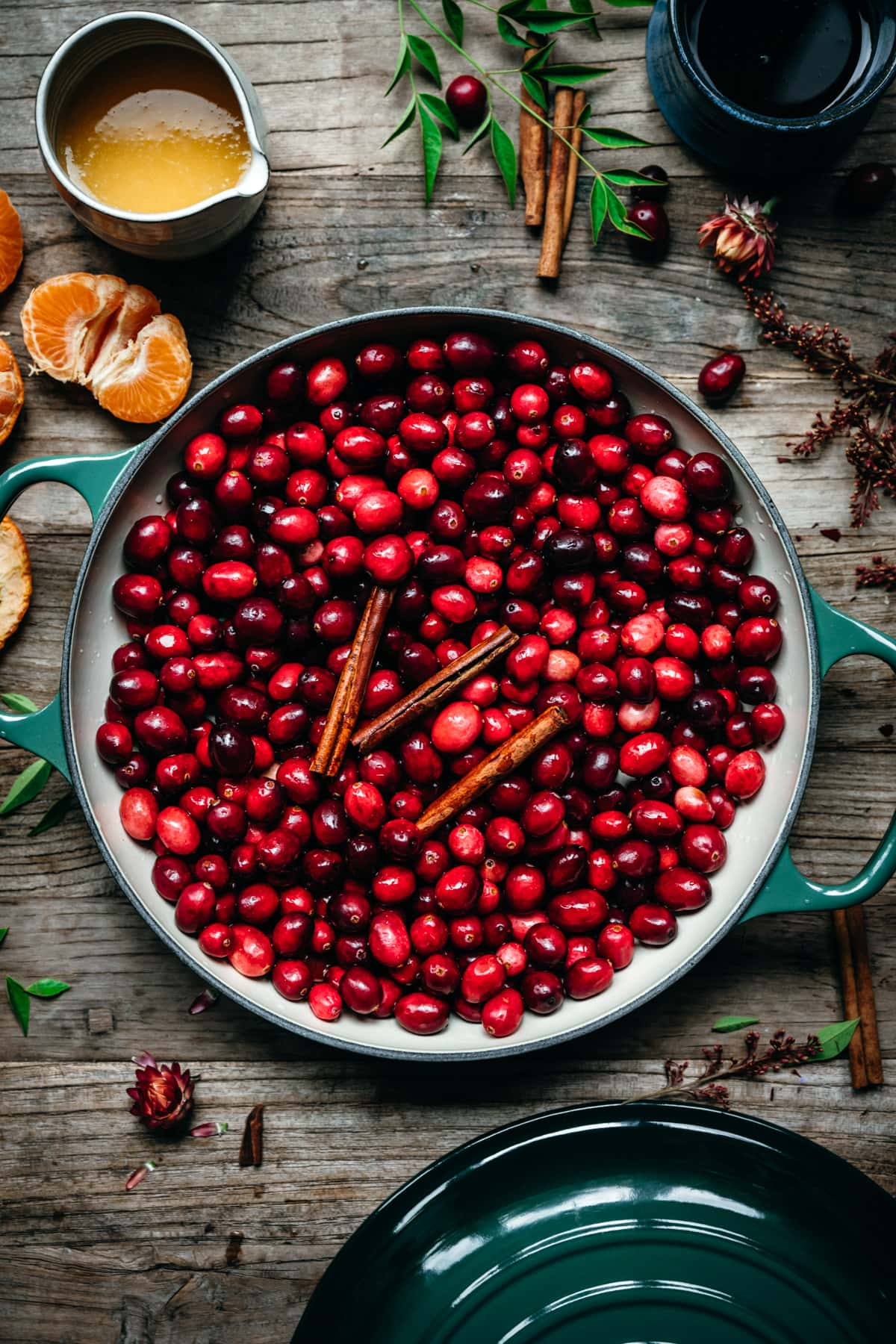 overhead view of fresh cranberries in a pot with cinnamon sticks.