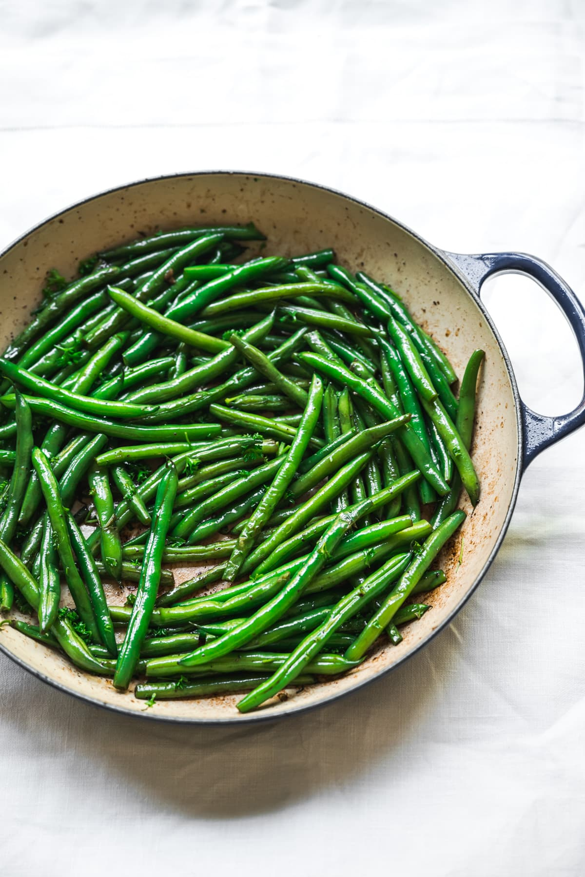 side view of sautéed green beans in a pan.