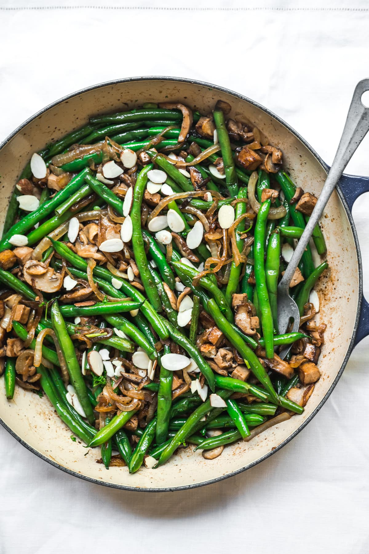 overhead view of vegan green beans with tofu bacon, mushrooms and caramelized onions in pan.