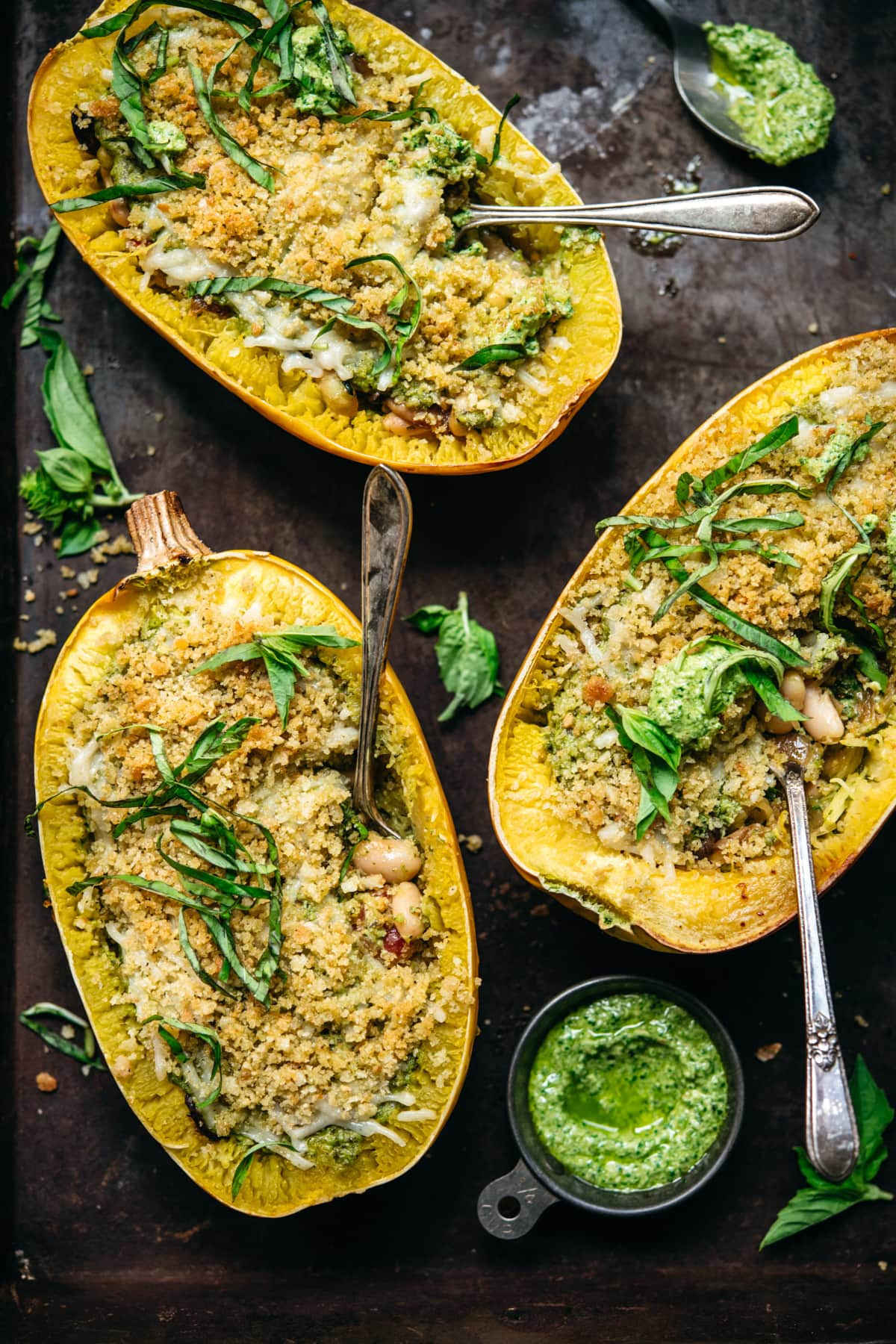 overhead view of spaghetti squash filled with pesto, white beans and topped with breadcrumbs.