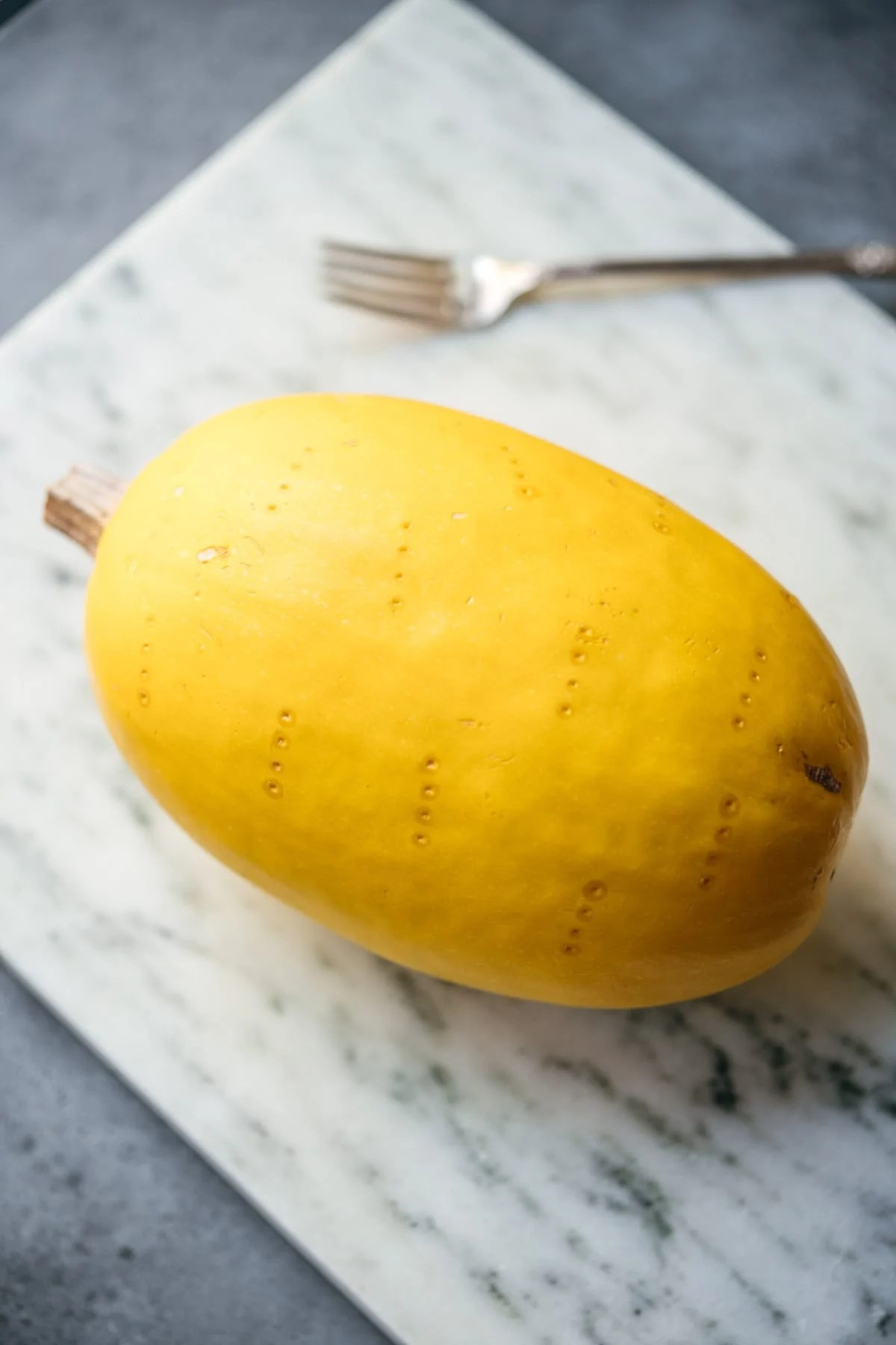 close up side view of whole spaghetti squash with fork marks.