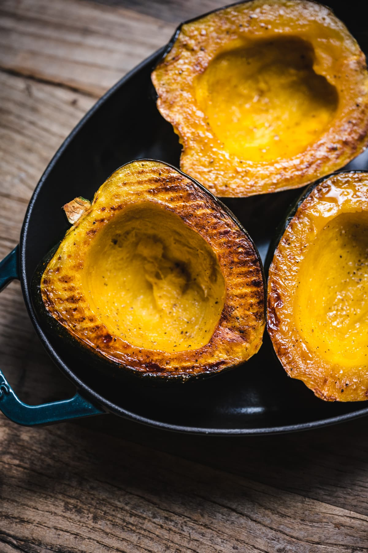 side view of roasted acorn squash half in a pan.