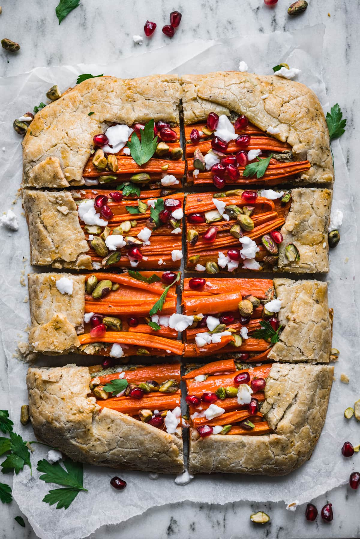 overhead view of sliced carrot tart with pomegranate, pesto and pistachios.