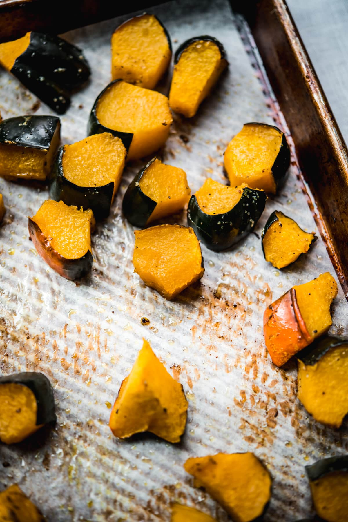 side view of roasted acorn squash on a sheet pan.