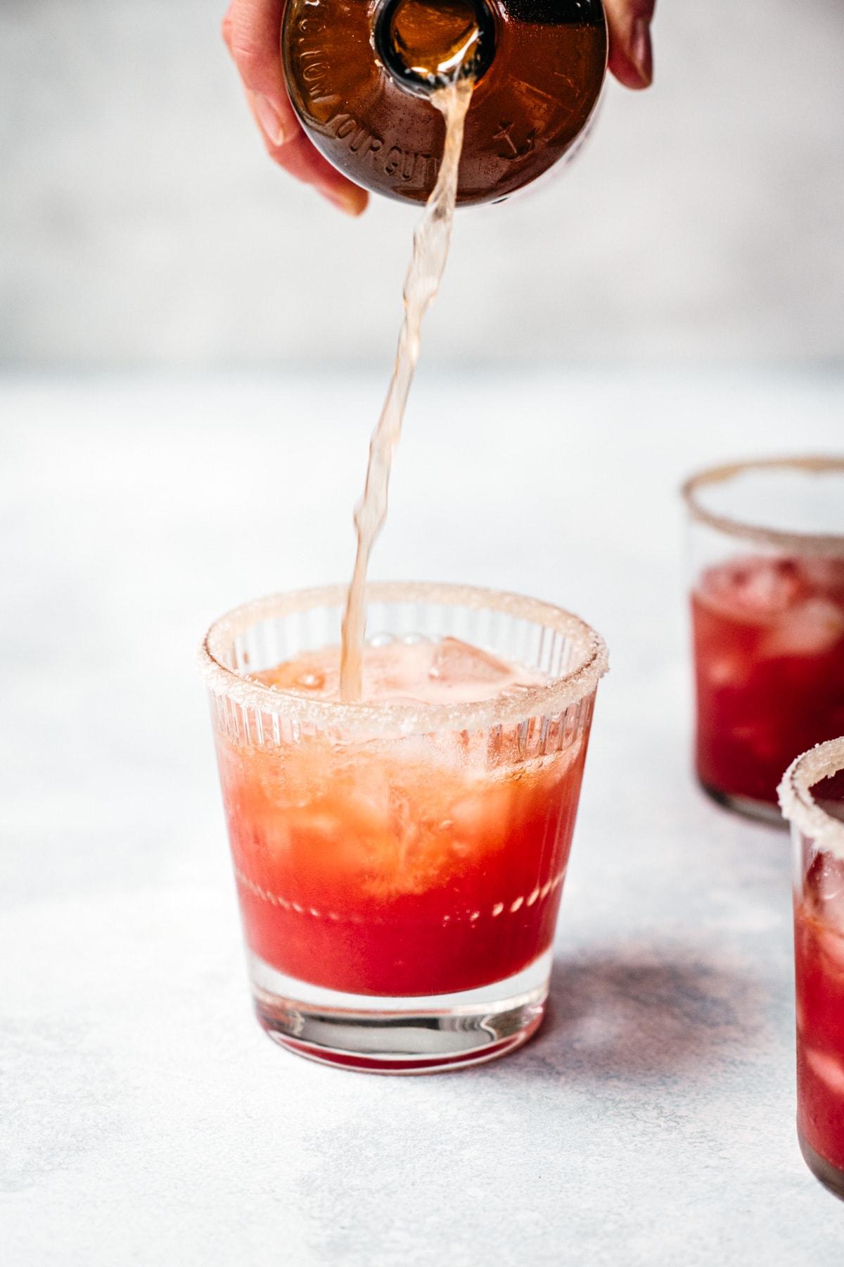 pouring kombucha into a blood orange margarita.