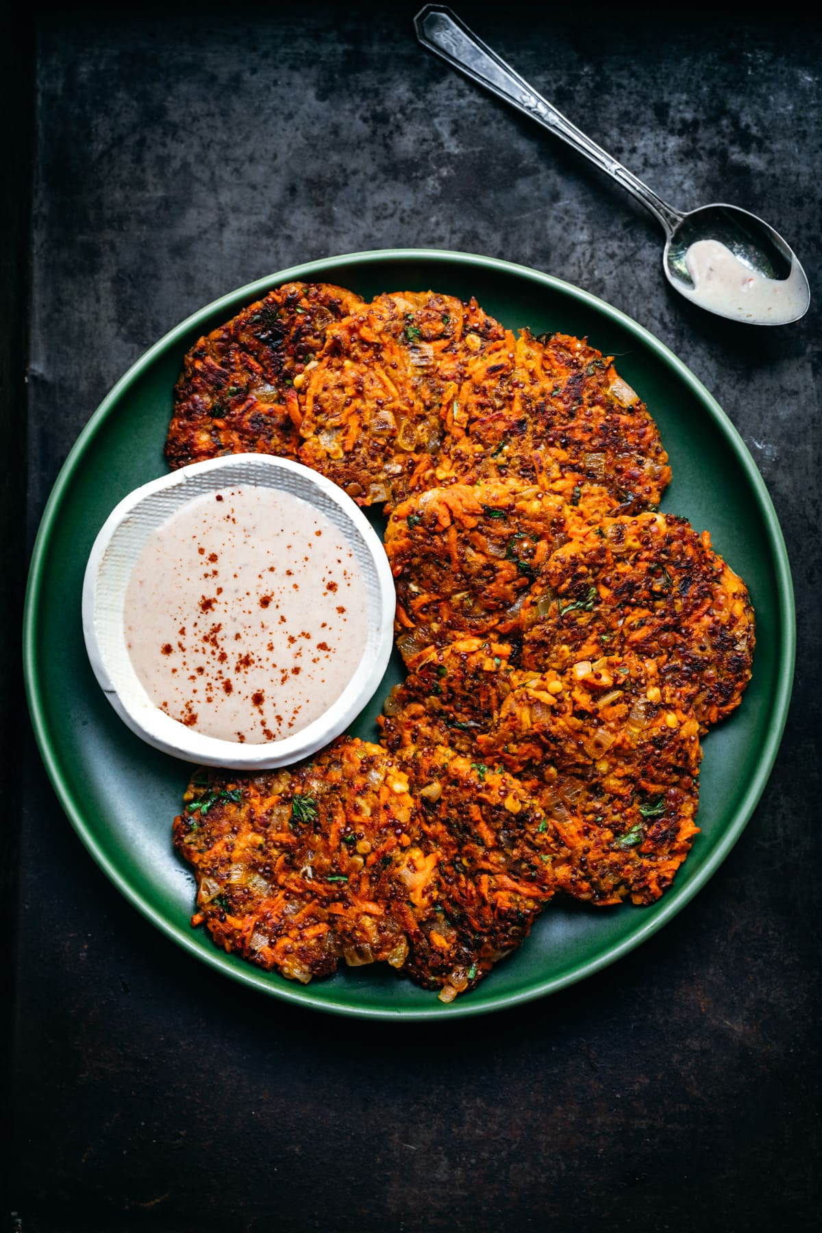 close up overhead view of vegan carrot fritters on a green plate with harissa yogurt sauce on the side.